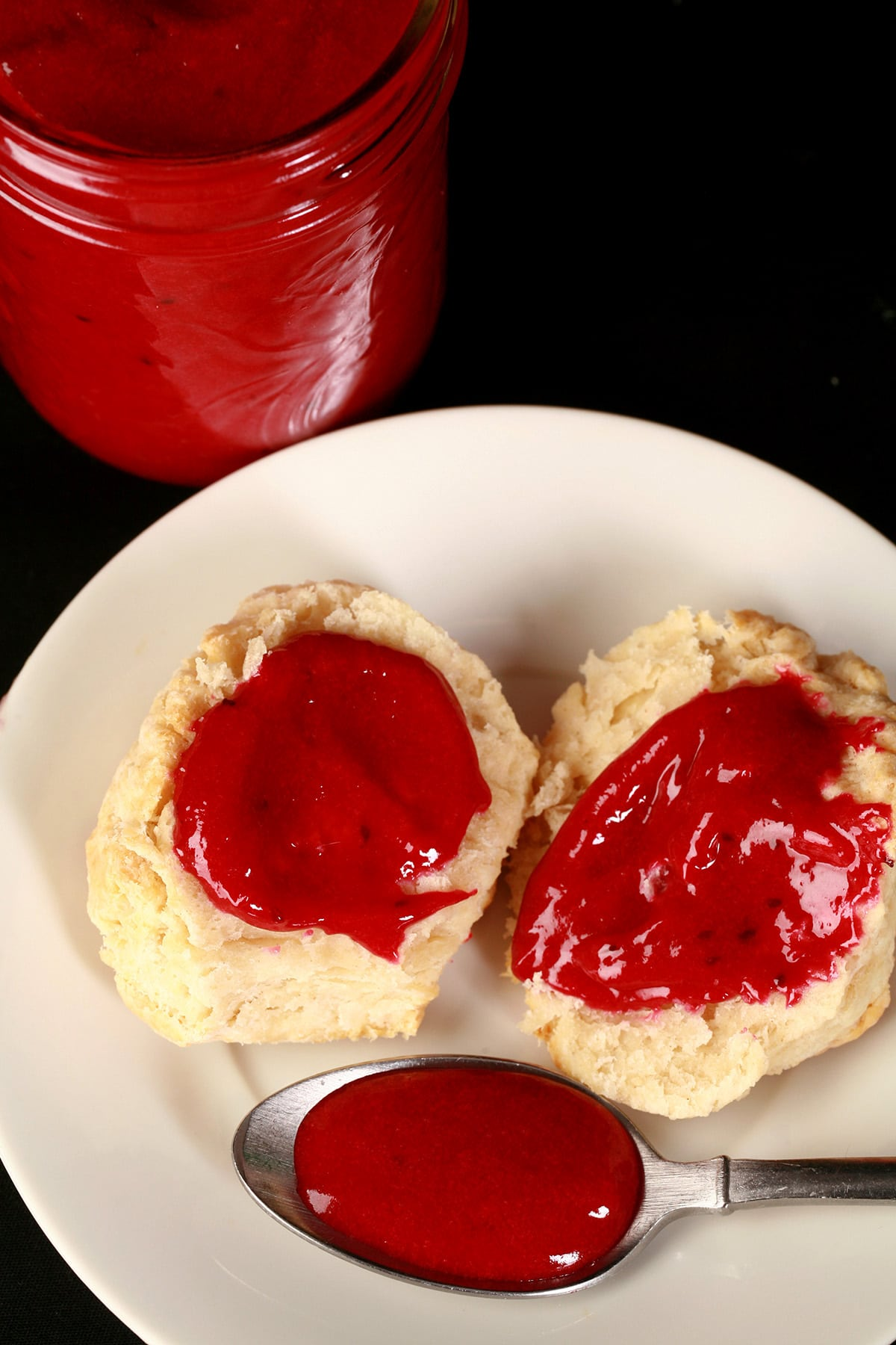 2 biscuits topped with blackcurrant curd, along with a spoon of the curd on the same plate.