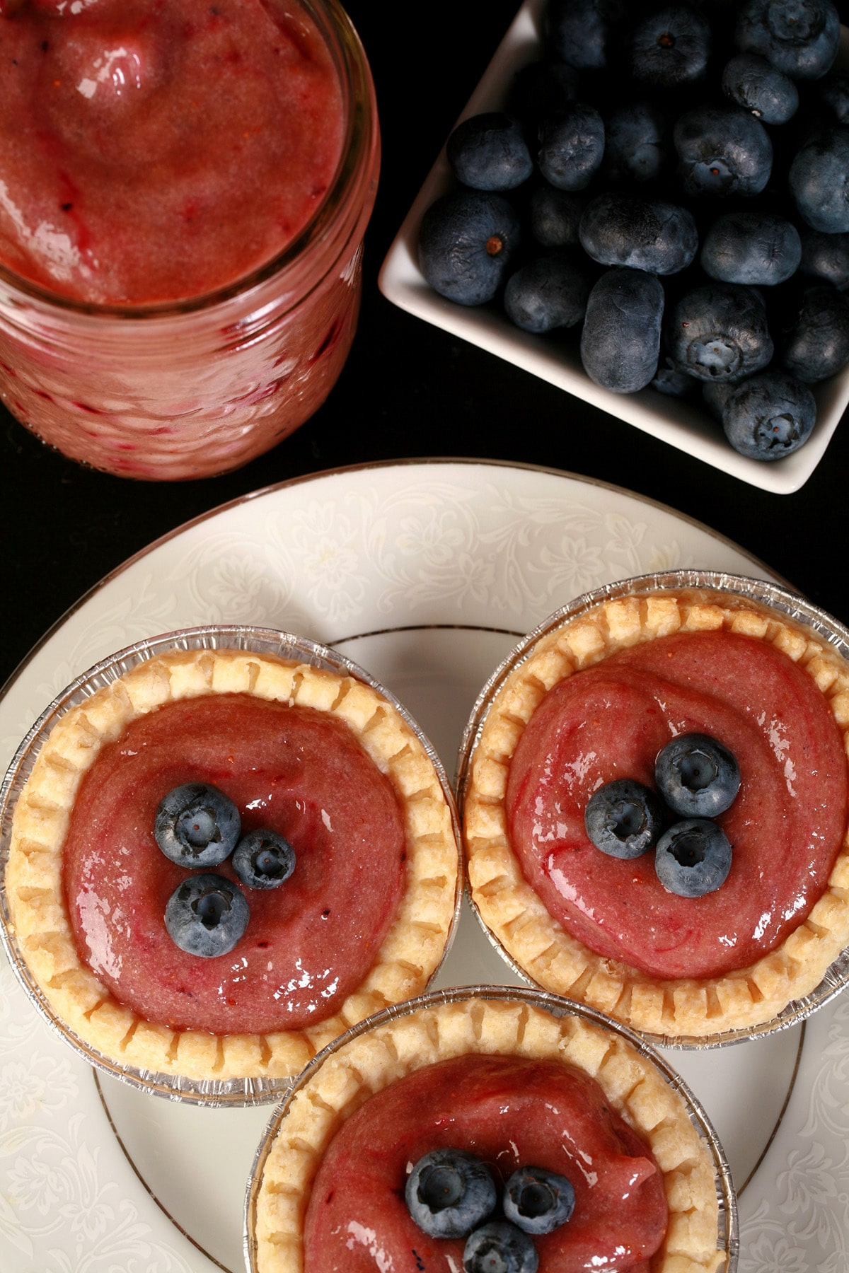 3 blueberry tarts on a plate, next to a jar of curd and a bowl of blueberries.
