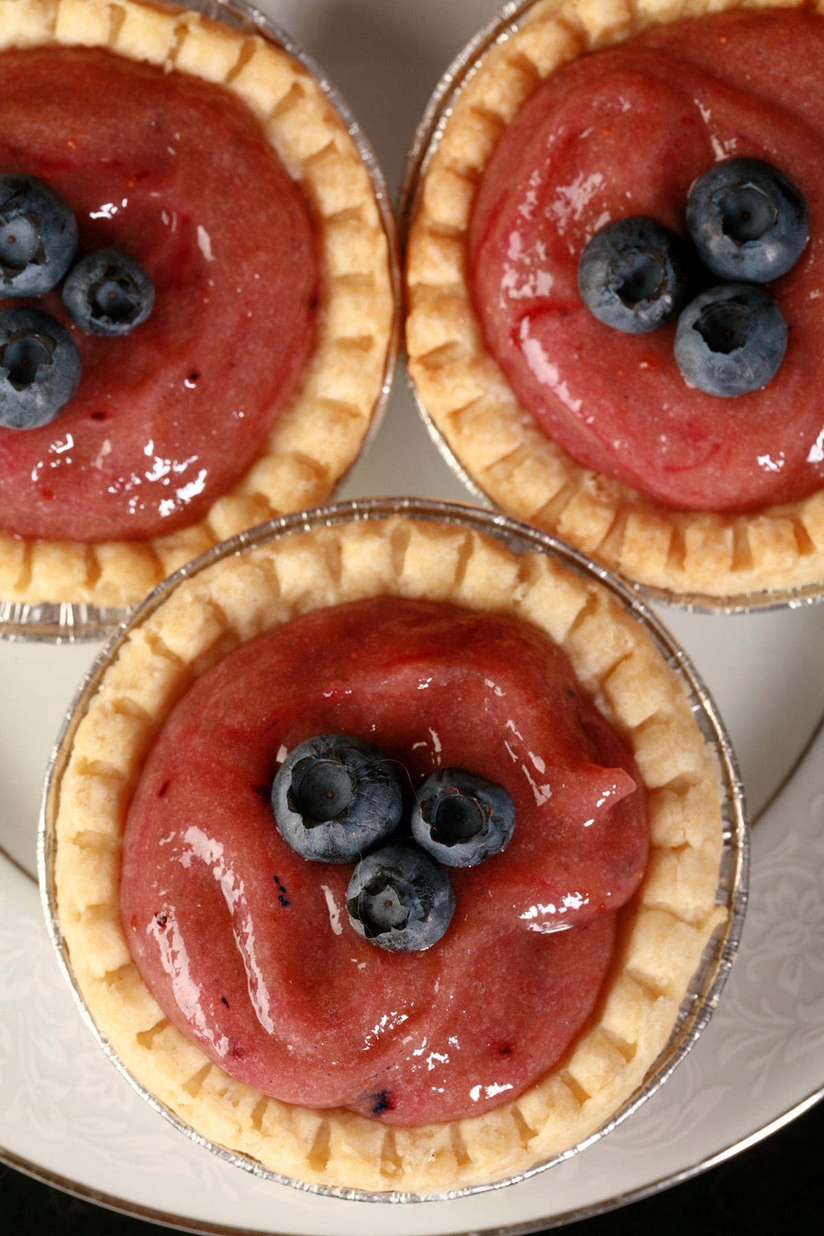 3 blueberry tarts on a plate.