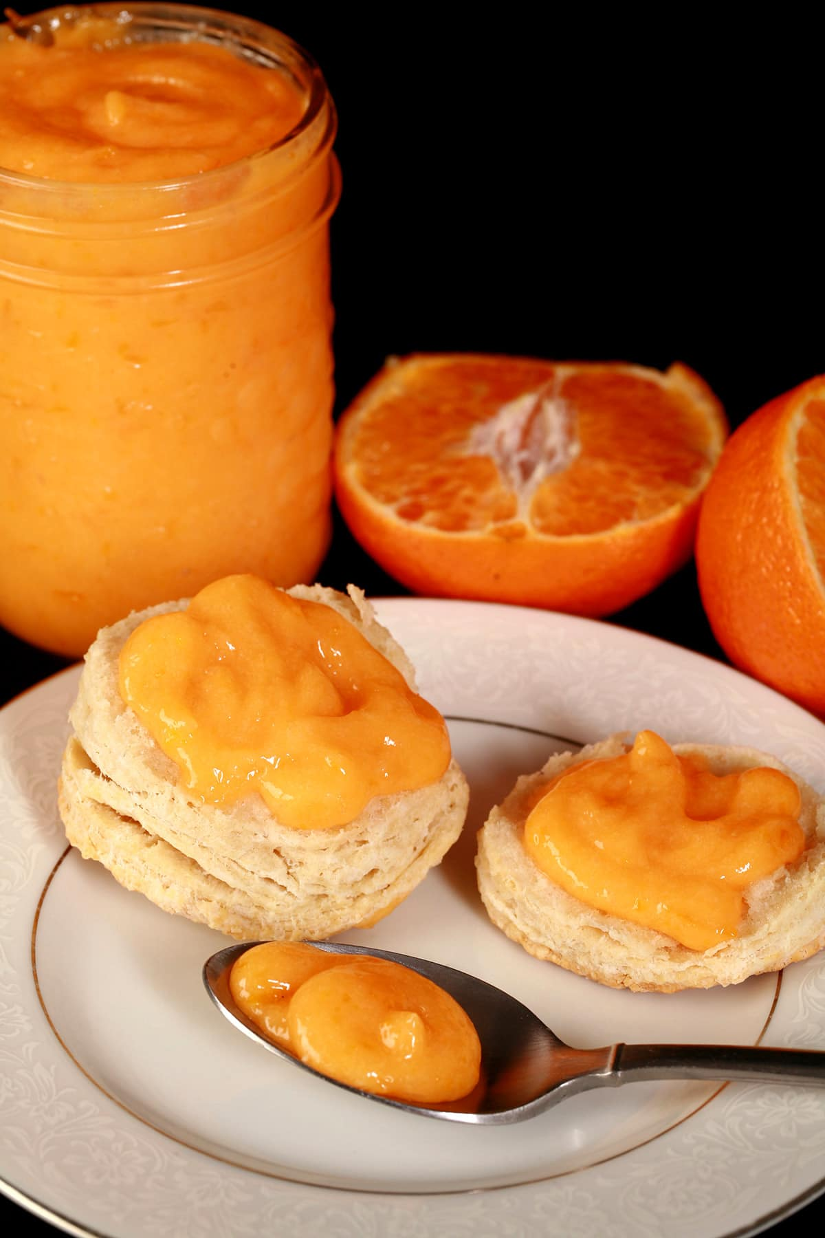 A sliced biscuit topped with orange curd, on a plate. There is a spoon of curd on the plate, and a jar of it next to the plate.
