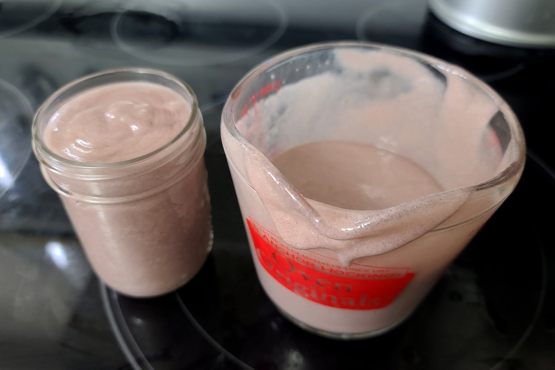 A jar of grape curd next to a glass measuring cup of fresh curd.