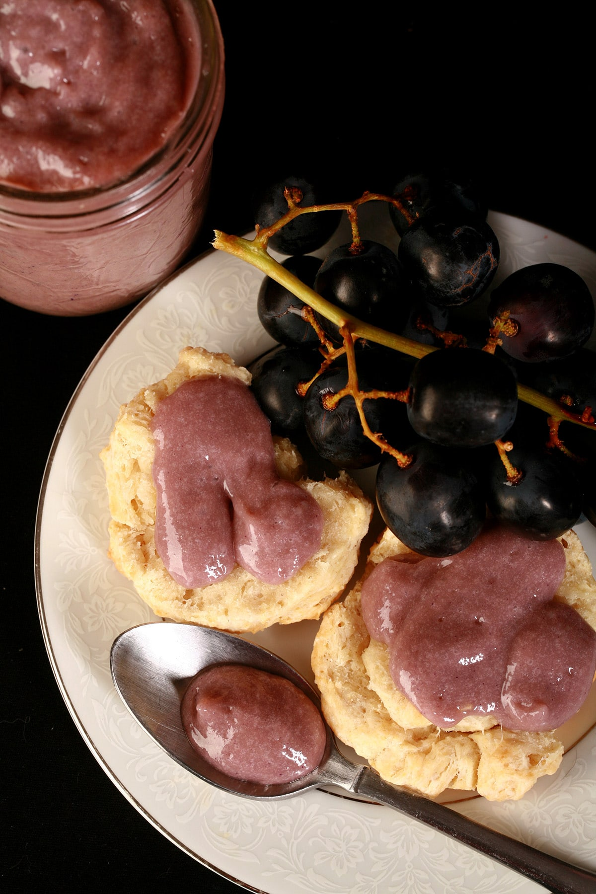 Two biscuits with grape curd on a plate, along with some concord grapes and a spoon of curd.