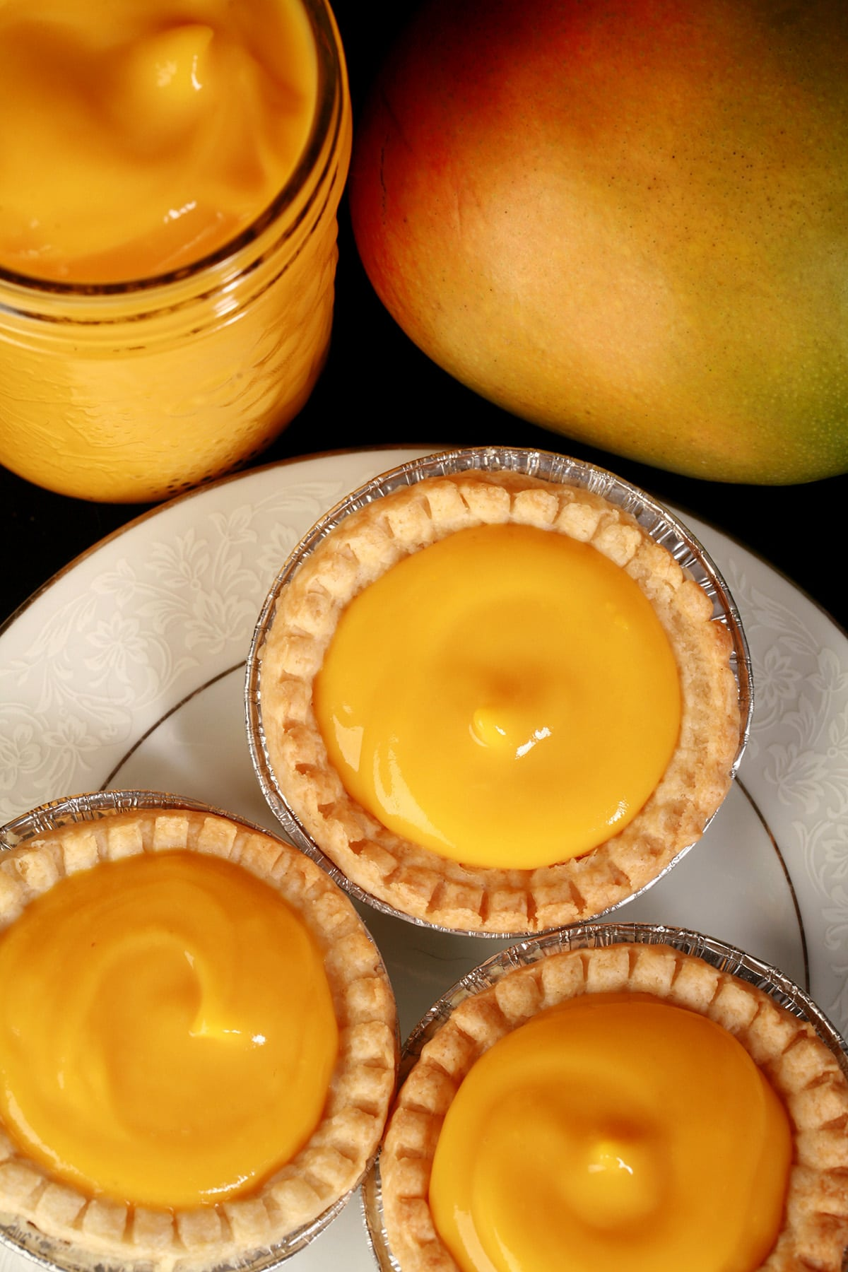 3 mango tarts on a plate, with a jar of mango curd and a mango behind the plate.