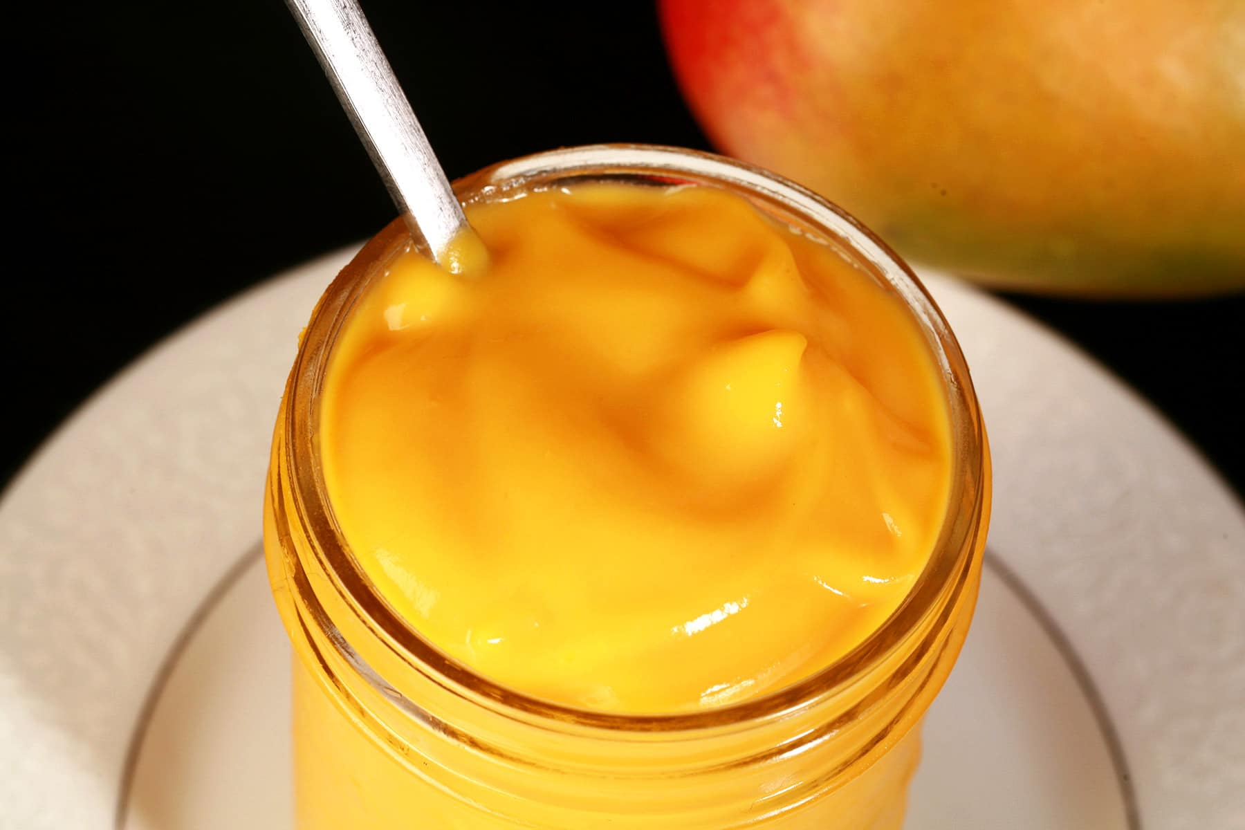 A jar of mango curd on a plate, with a whole mango behind it.