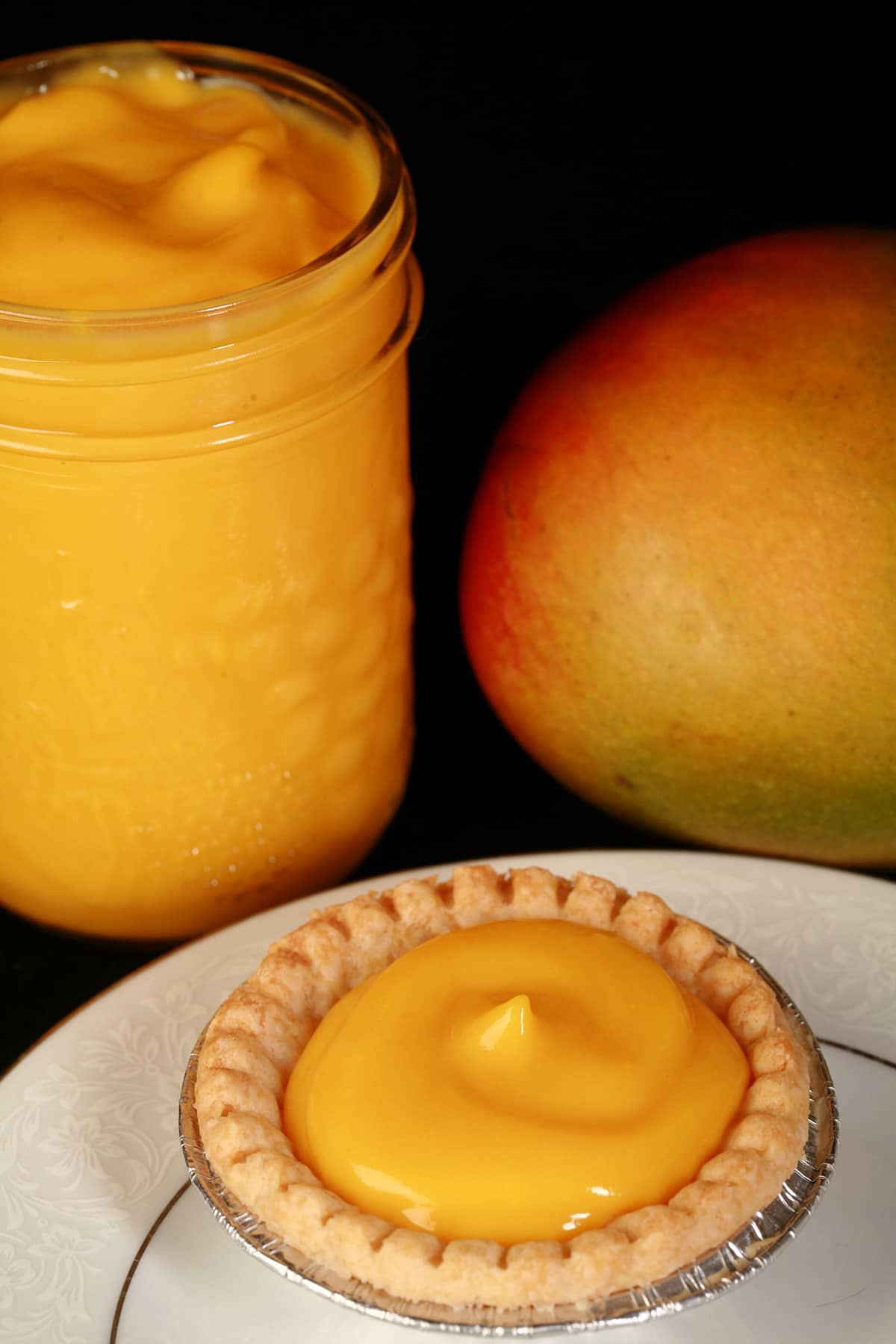 A mango tart on a plate, with a jar of mango curd and a mango behind the plate.