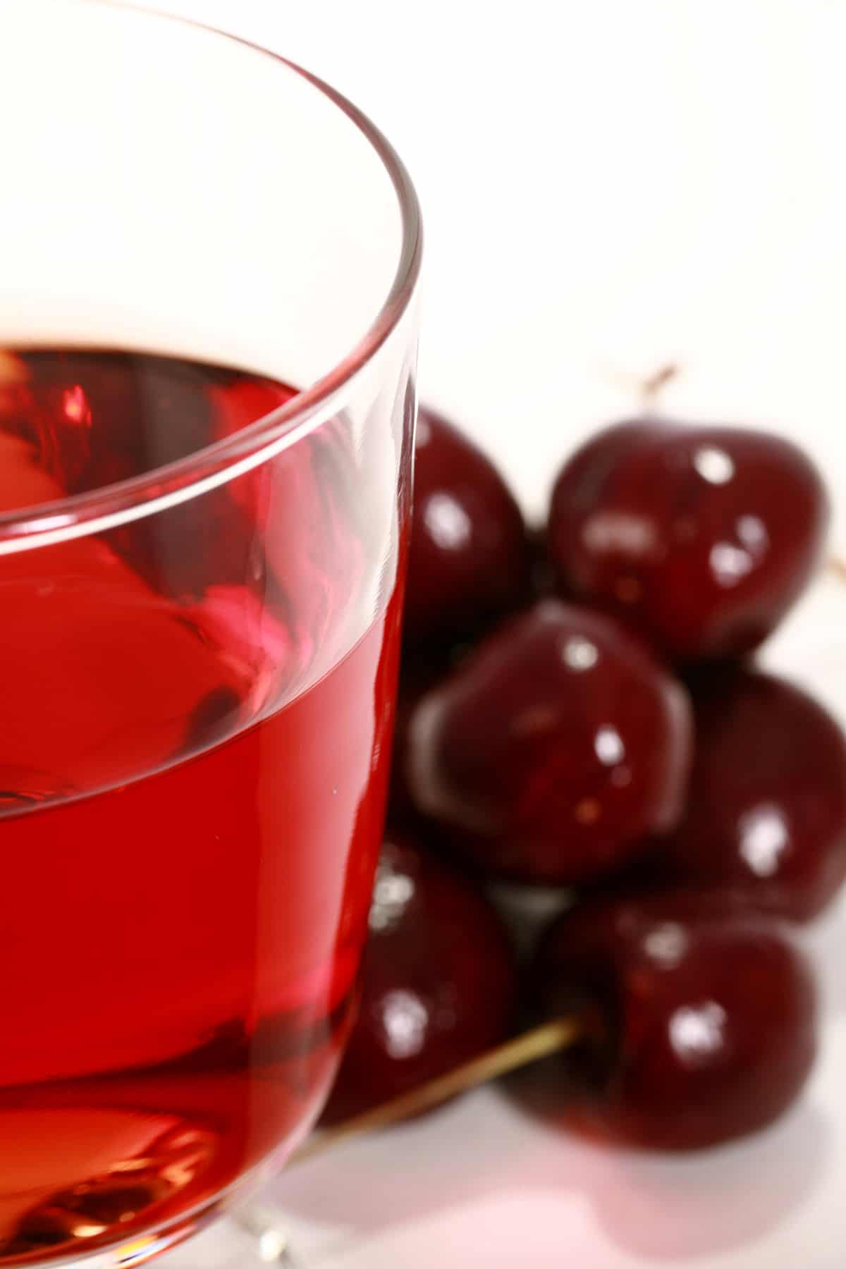 A glass of black cherry mead, next to a pile of black cherries.