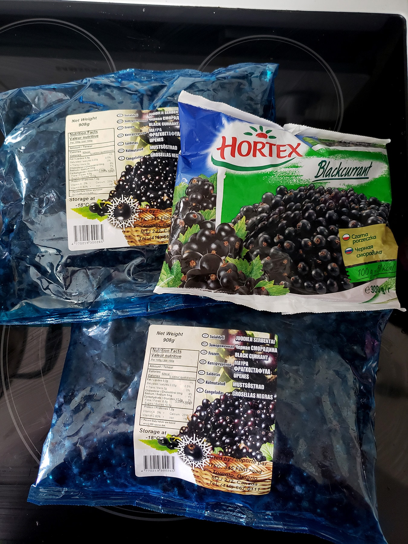 Several bags of frozen blackcurrants, on a stove top.