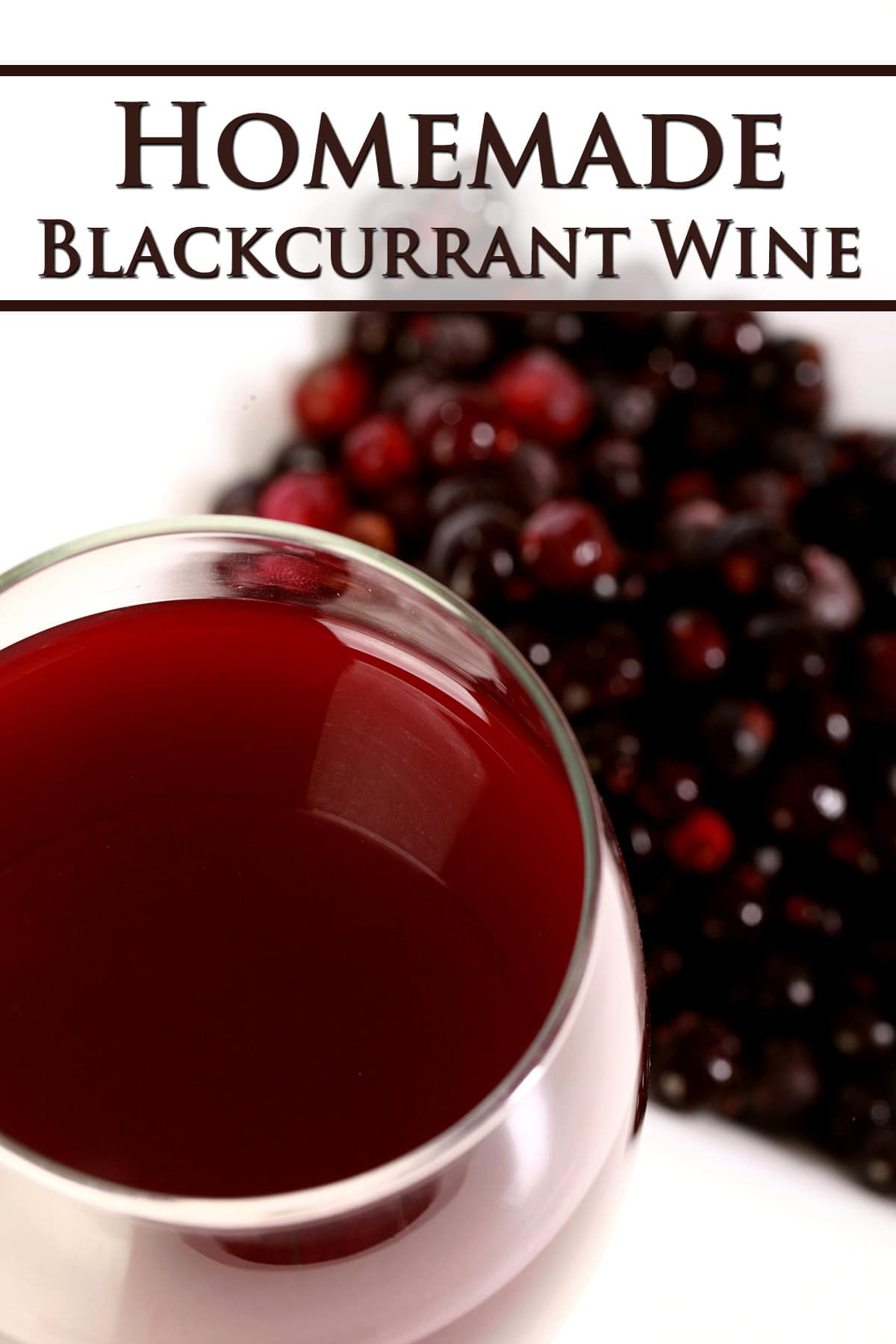A glass of blackcurrant wine, with a small dish of black currants next to it.