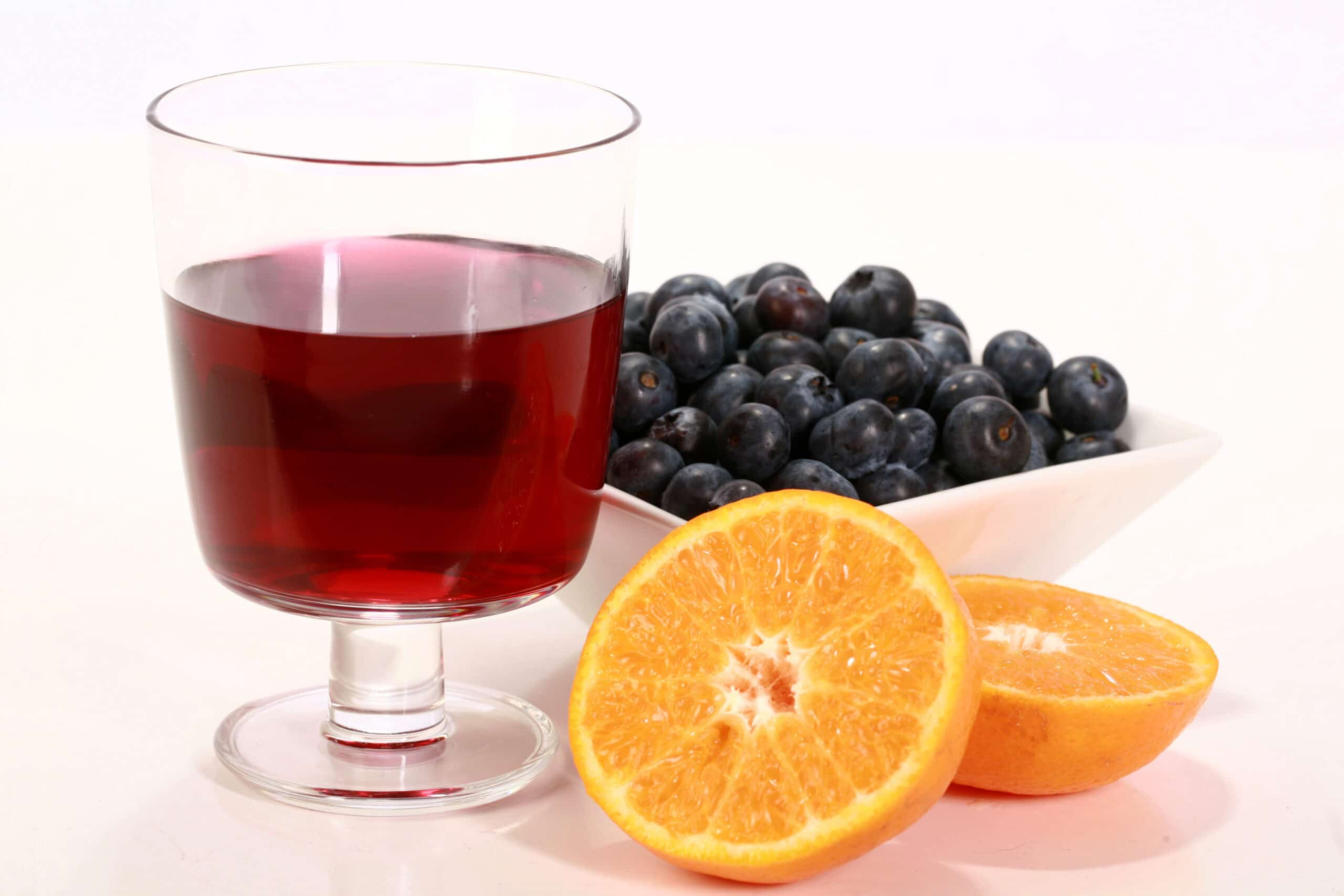 A wine glass of a medium purple blueberry clementine mead, with a dish of blueberries and a halved clementine next to it.