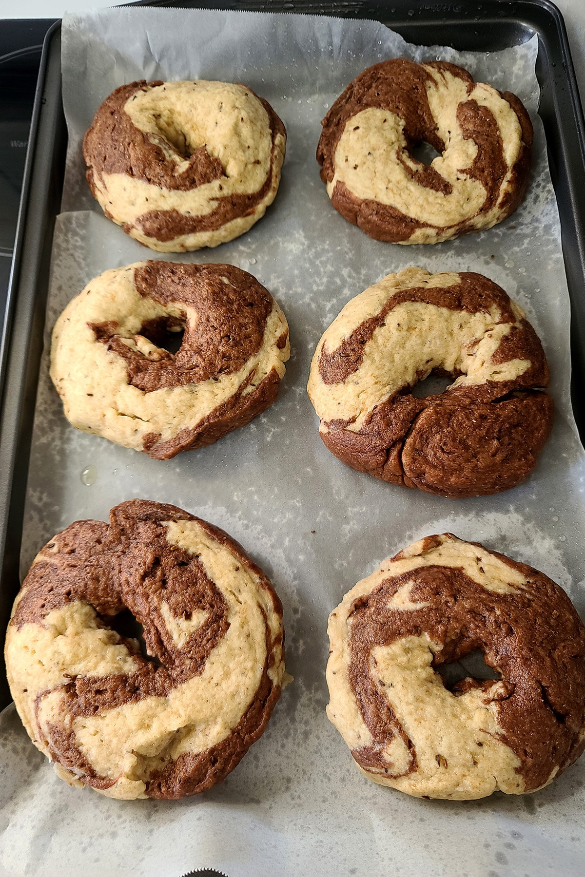 6 unbaked marbled rye bagels on a parchment lined baking sheet.