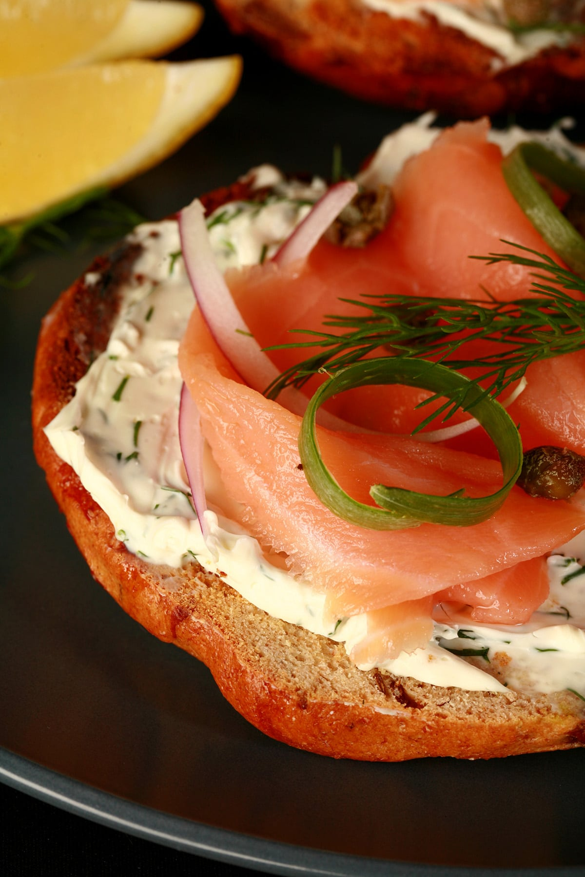 A toasted bagel open face sandwich with smoked salmon, cream cheese, capers, and onions.