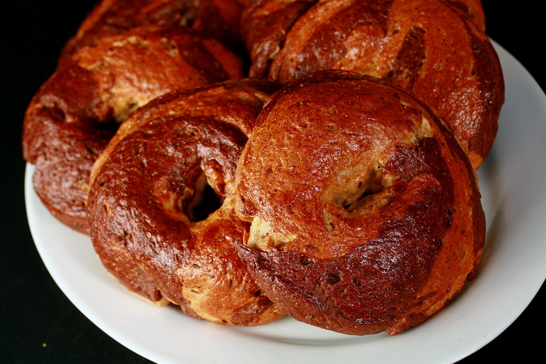 A plate of 6 golden brown marbled rye bagels.