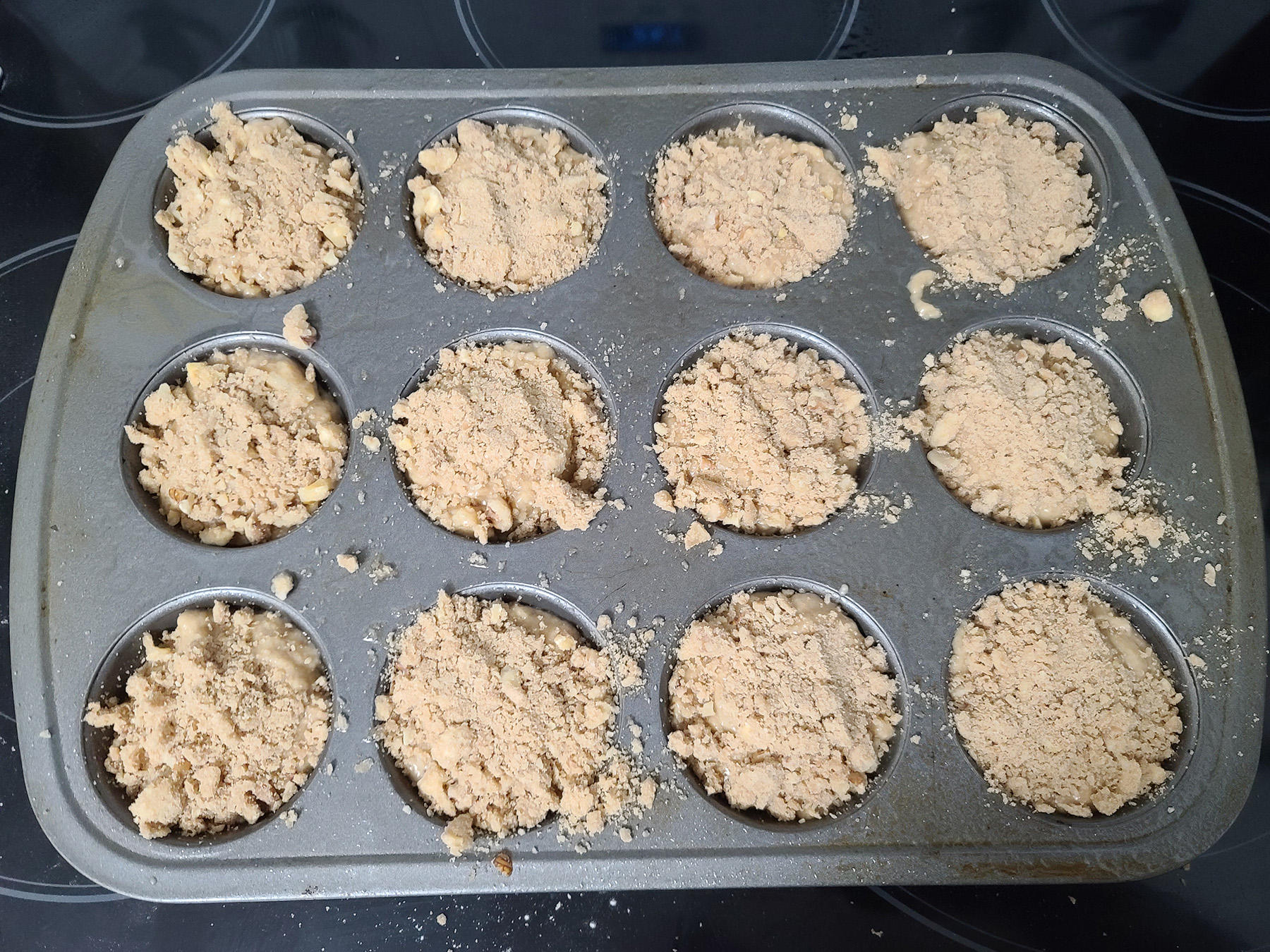 The batter in the muffin pan, with each cavity topped with streusel.