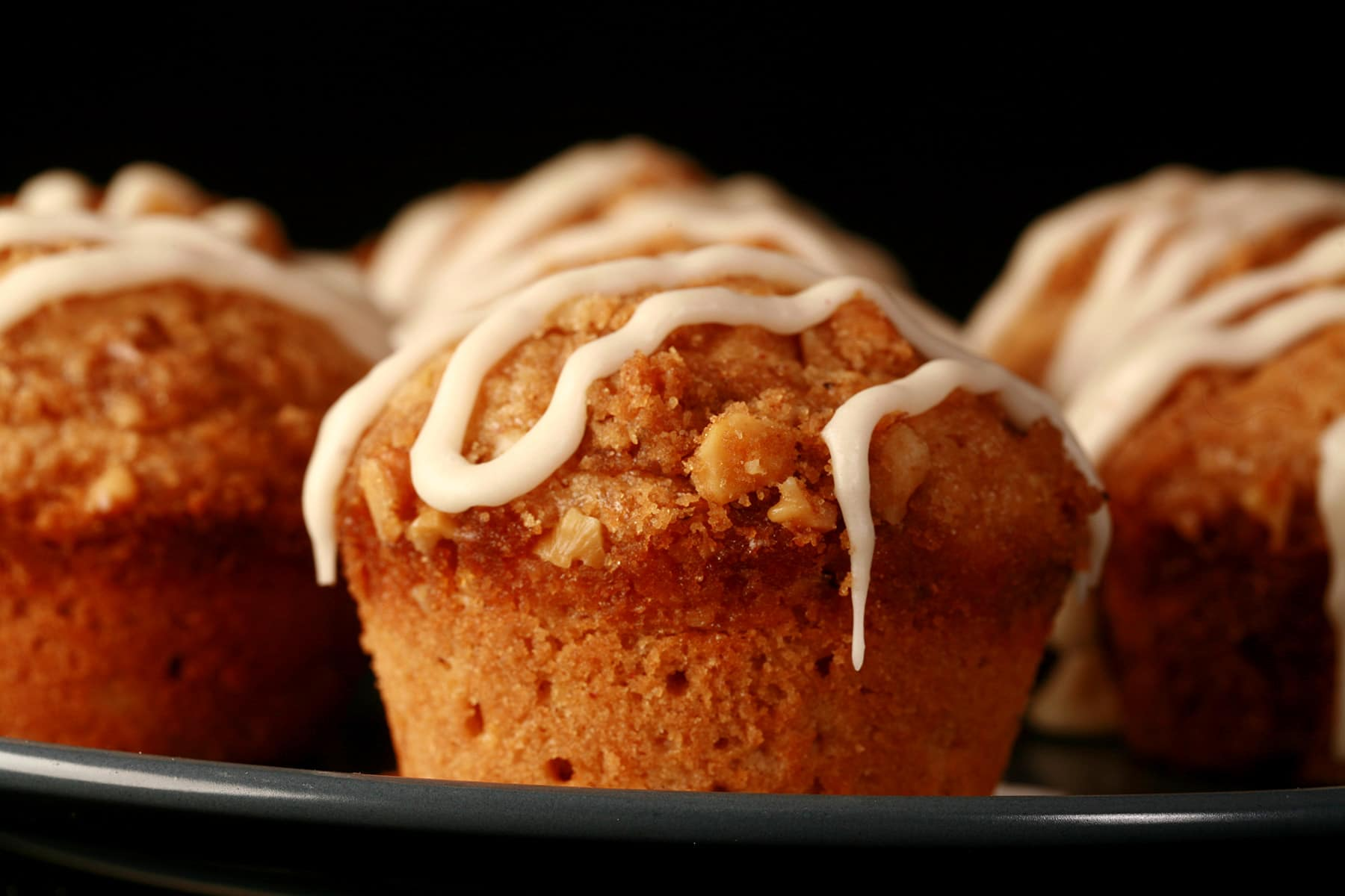 A plate of nutmeg coffee cake muffins, each drizzled with maple nutmeg glaze.