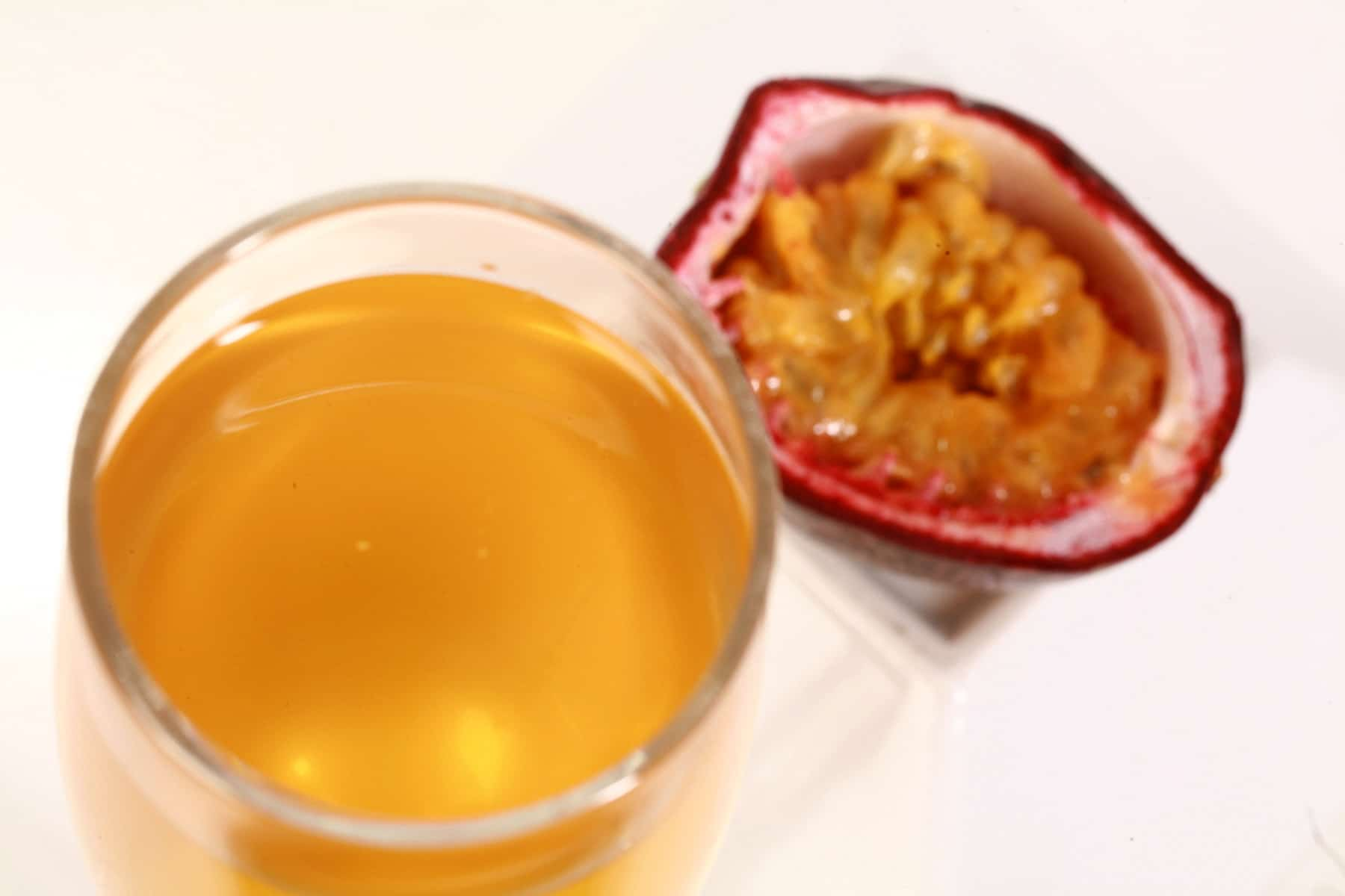 A flute of golden yellow passionfruit wine, next to a halved passionfruit.