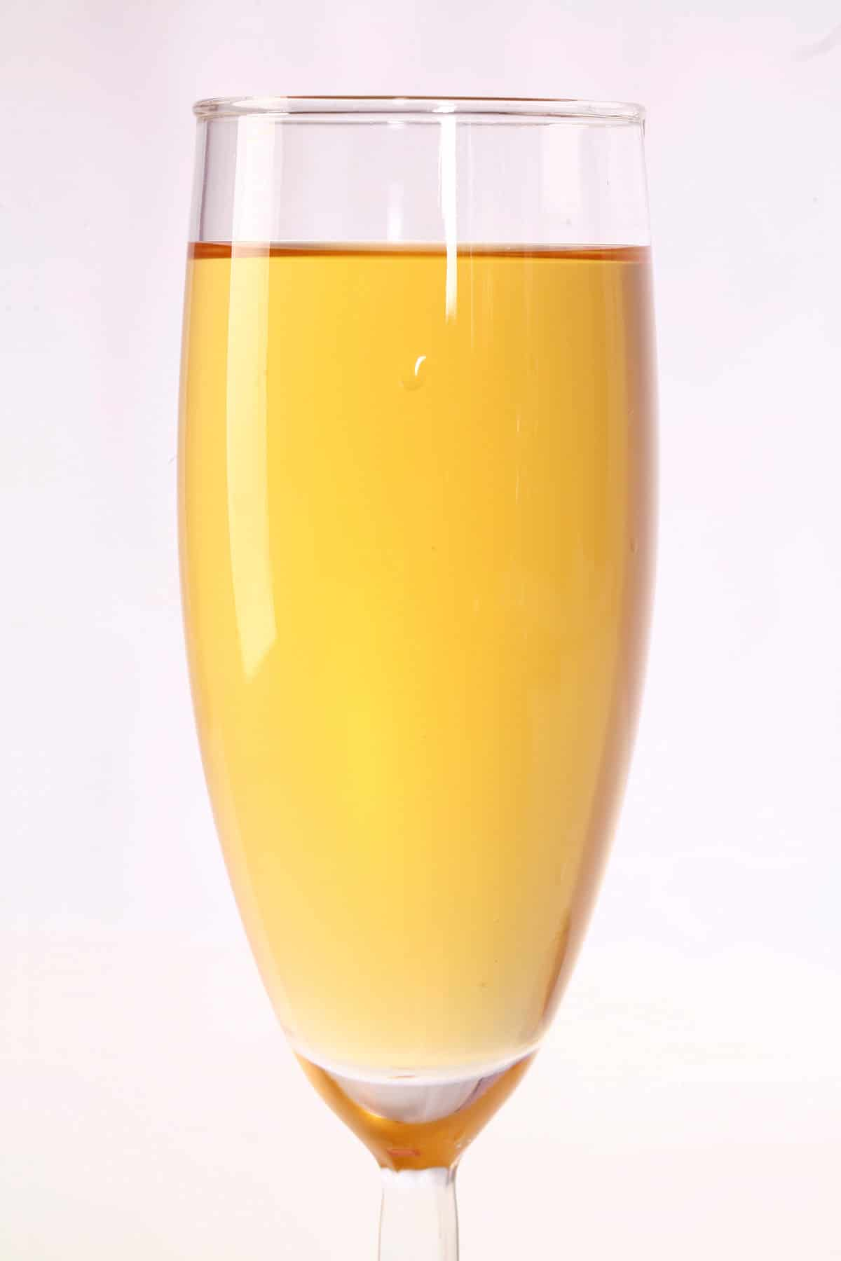 A flute of golden yellow passionfruit wine.