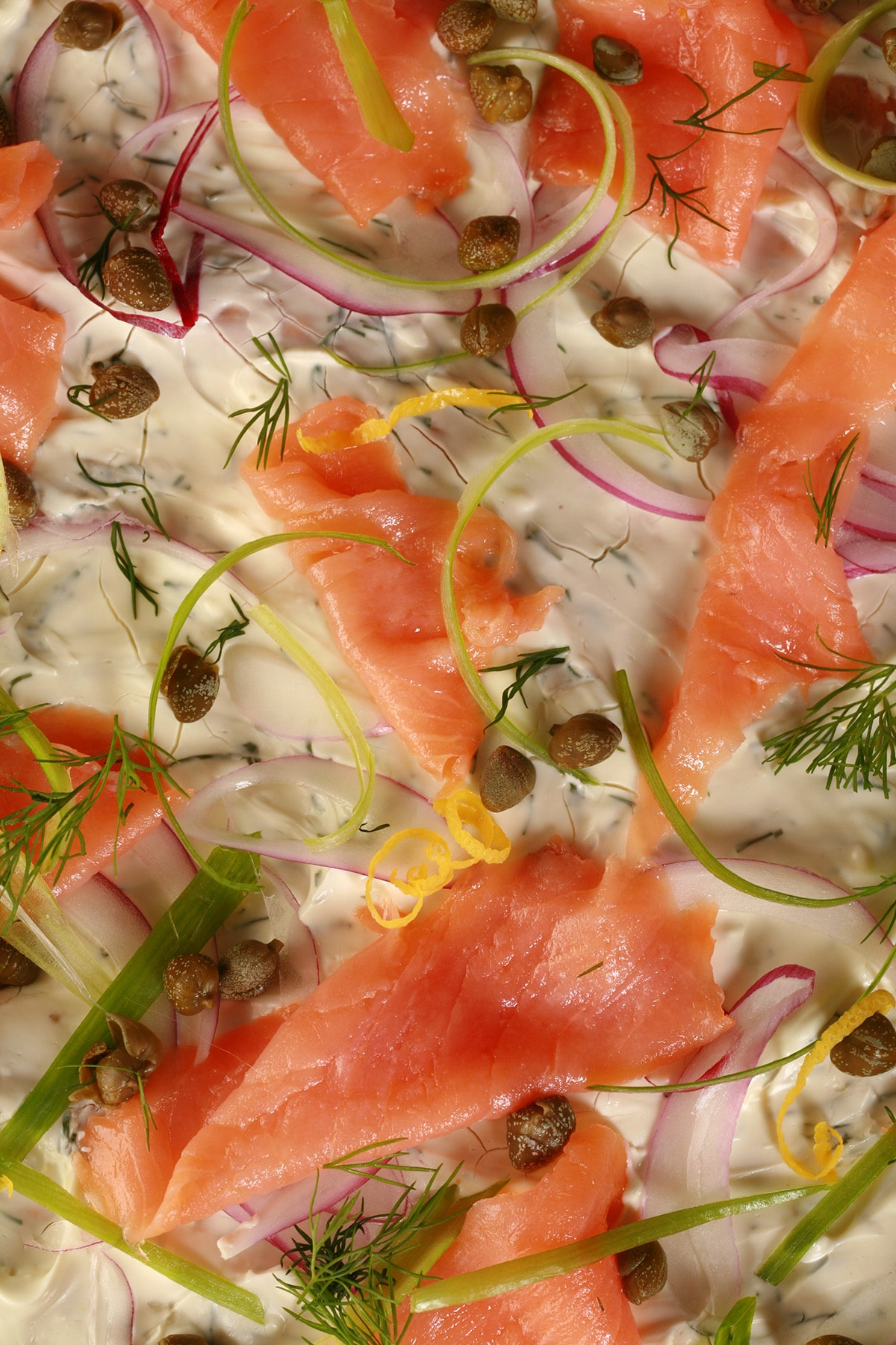 A close up view of smoked salmon pizza. The crust is rye, and it's topped with cream cheese sauce, smoked salmon, and other toppings.