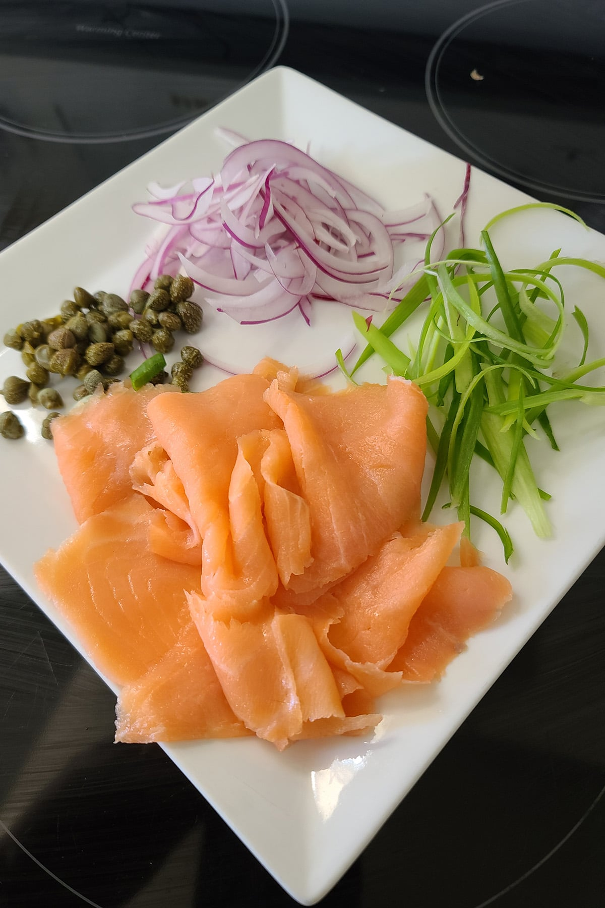 A plate with smoked salmon, green onion ribbons, slices of red onion, and drained capers.