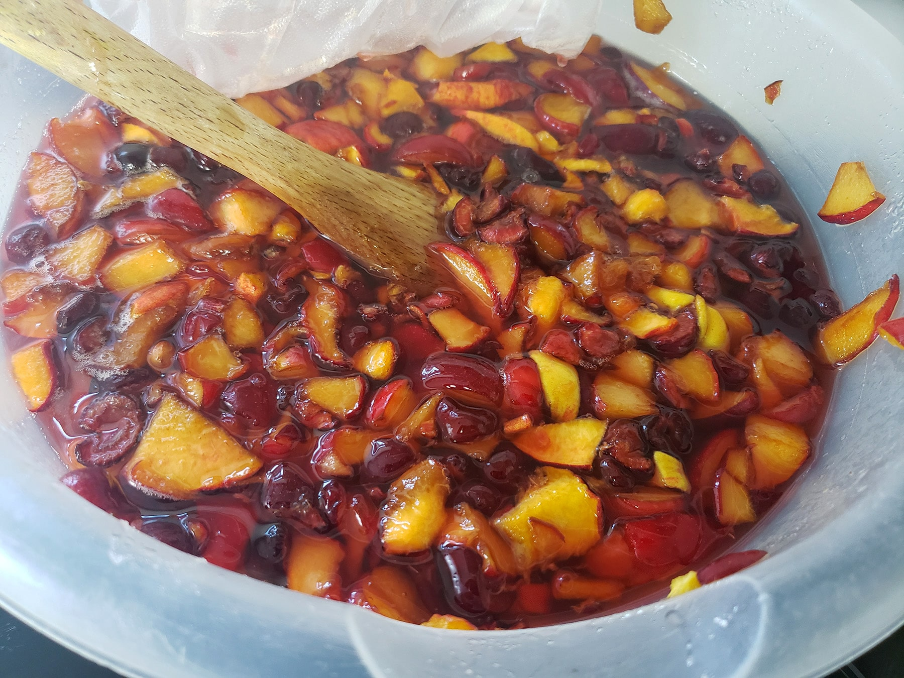 A big bowl of chopped stone fruit, macerating in a sugar syrup.
