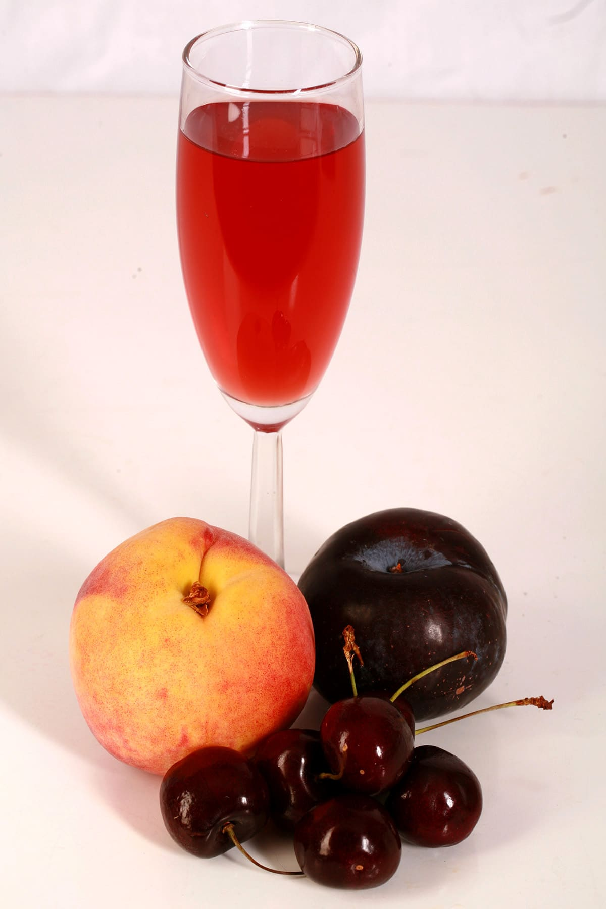 A tall glass of fruit punch-coloured stone fruit wine, next to a peach, a plum, and a few cherries.