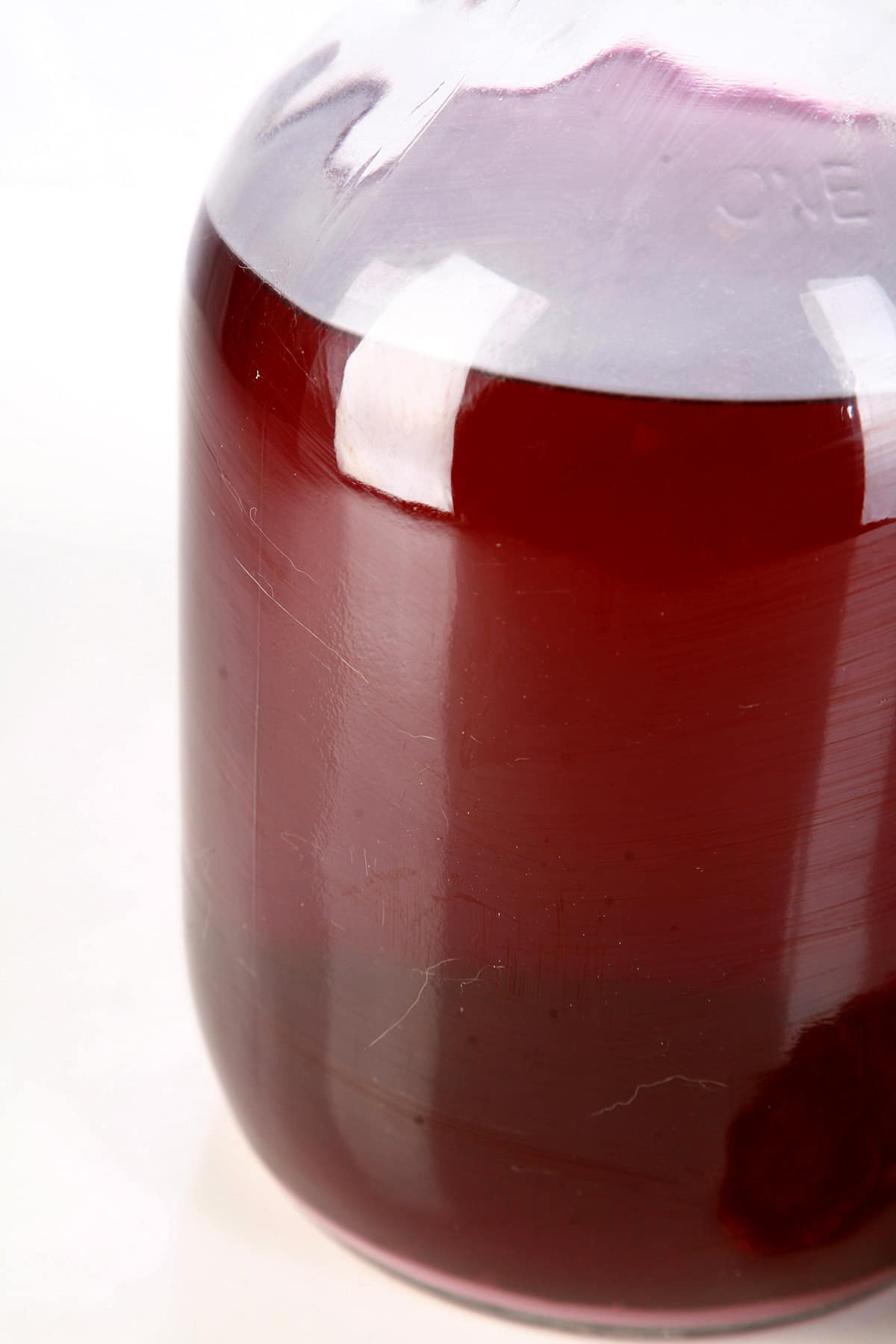 A glass carboy of homemade ube wine.