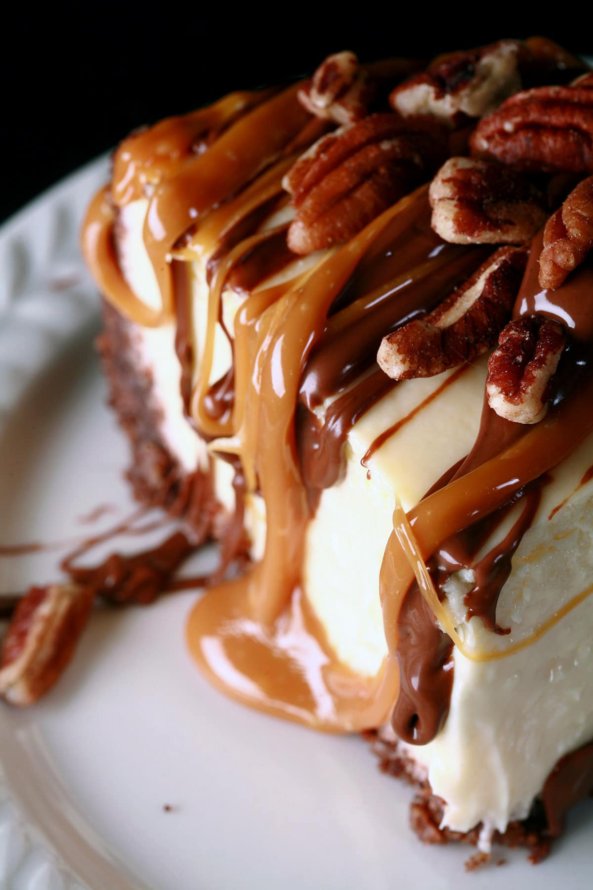 A close up view of a slice of turtle cheesecake.