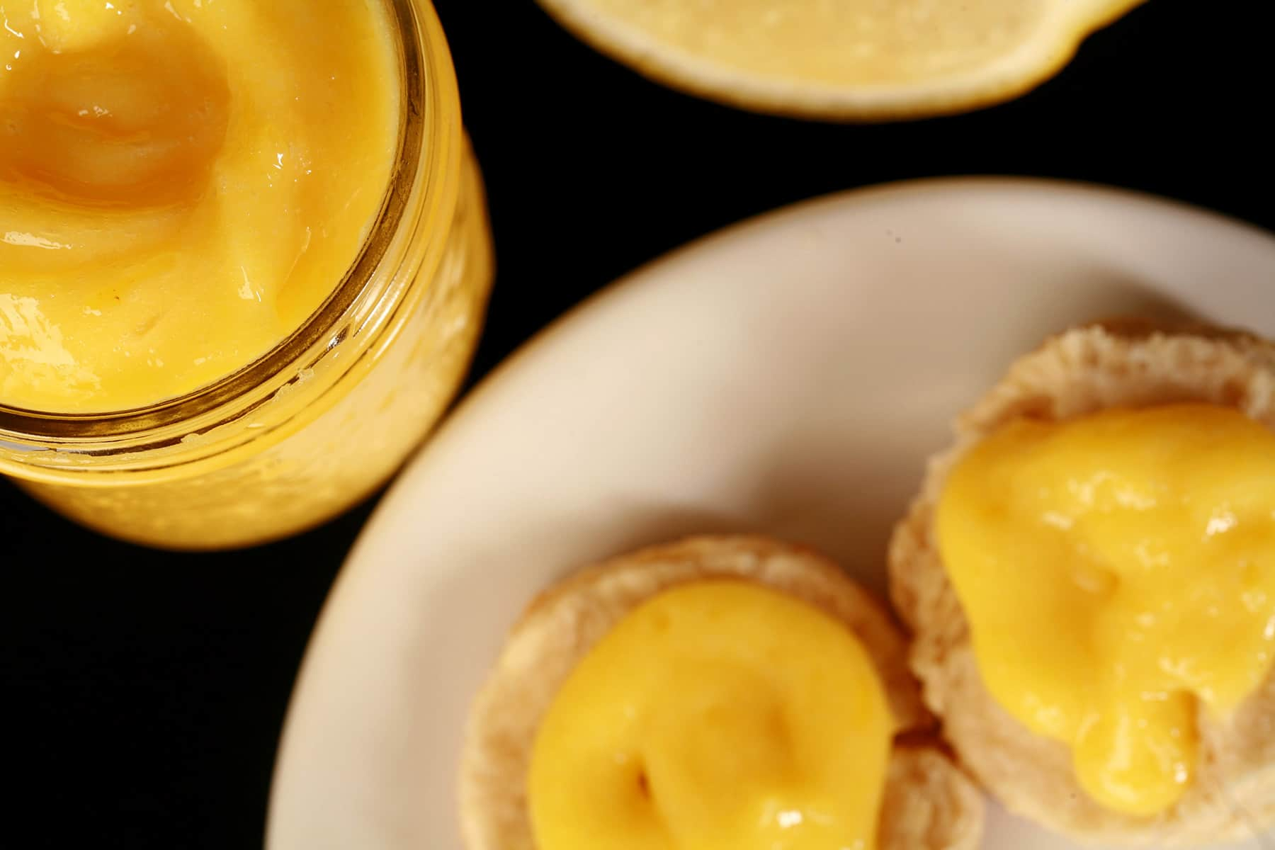 A jam jar of lemon curd on a plate, along with 2 biscuits topped with curd.