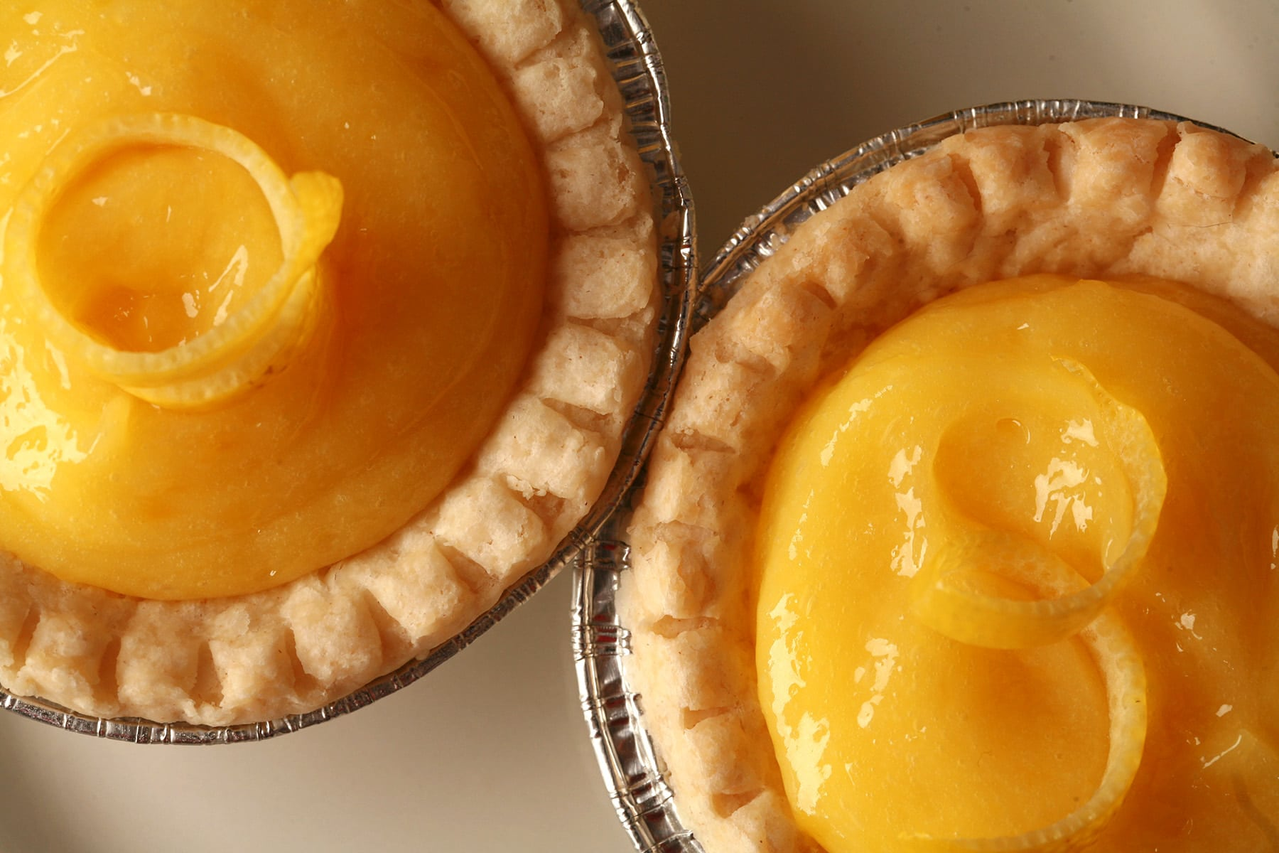 A close up view of two lemon tarts.
