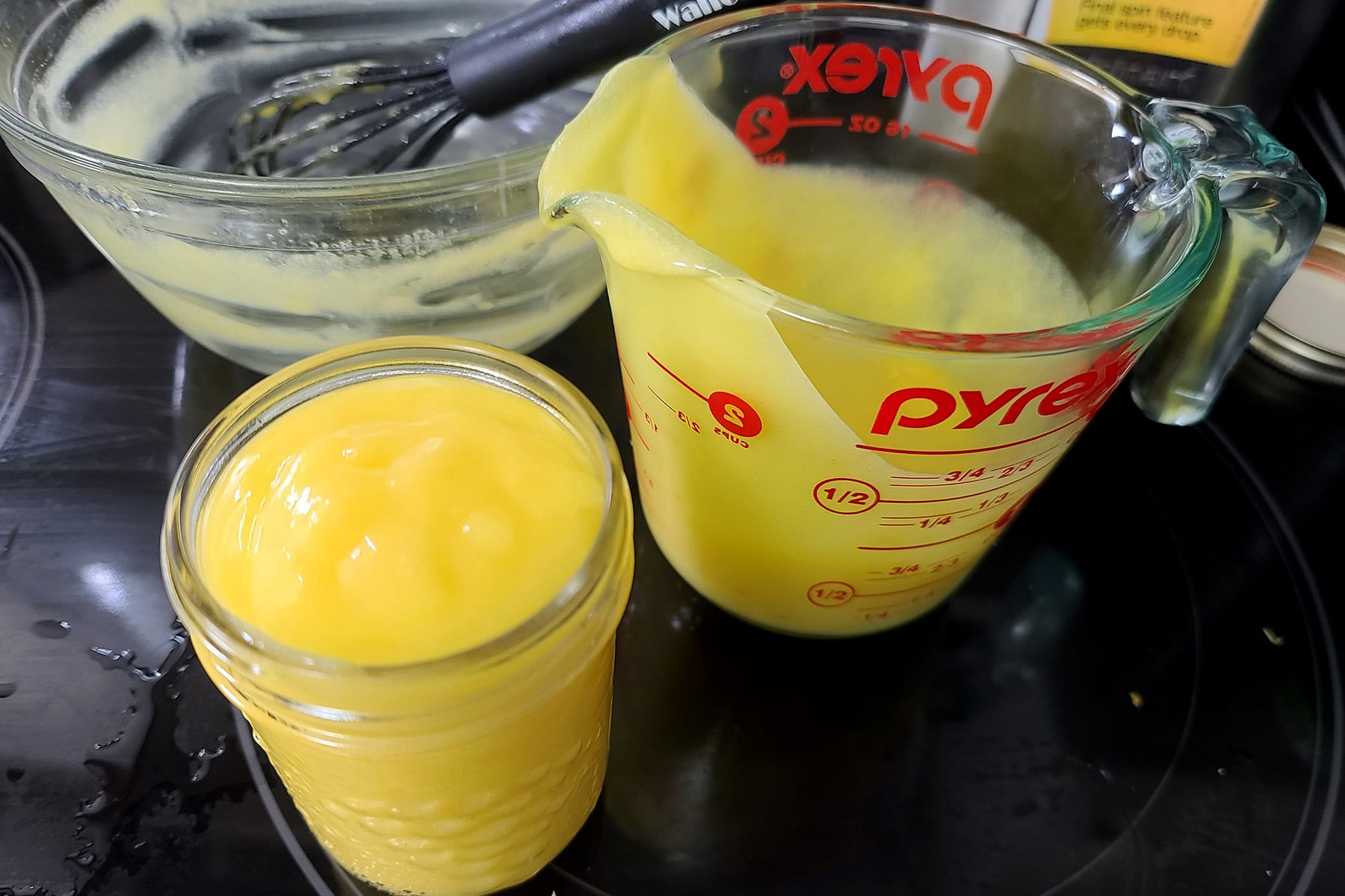 An empty mixing bowl, a glass measuring cup, and a jam jar filled with fresh lemon curd.