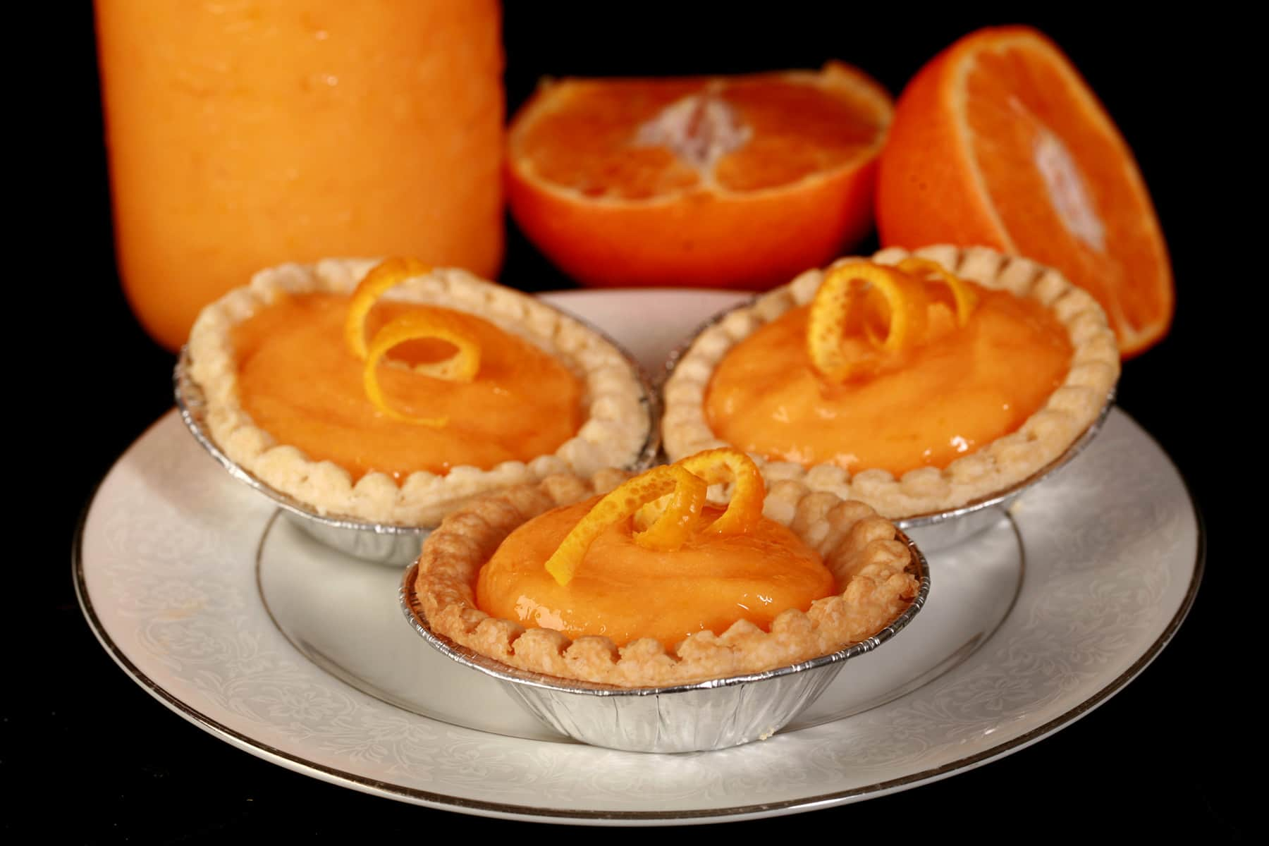 3 orange tarts on a plate. There is a jar of curd and an orange next to the plate.