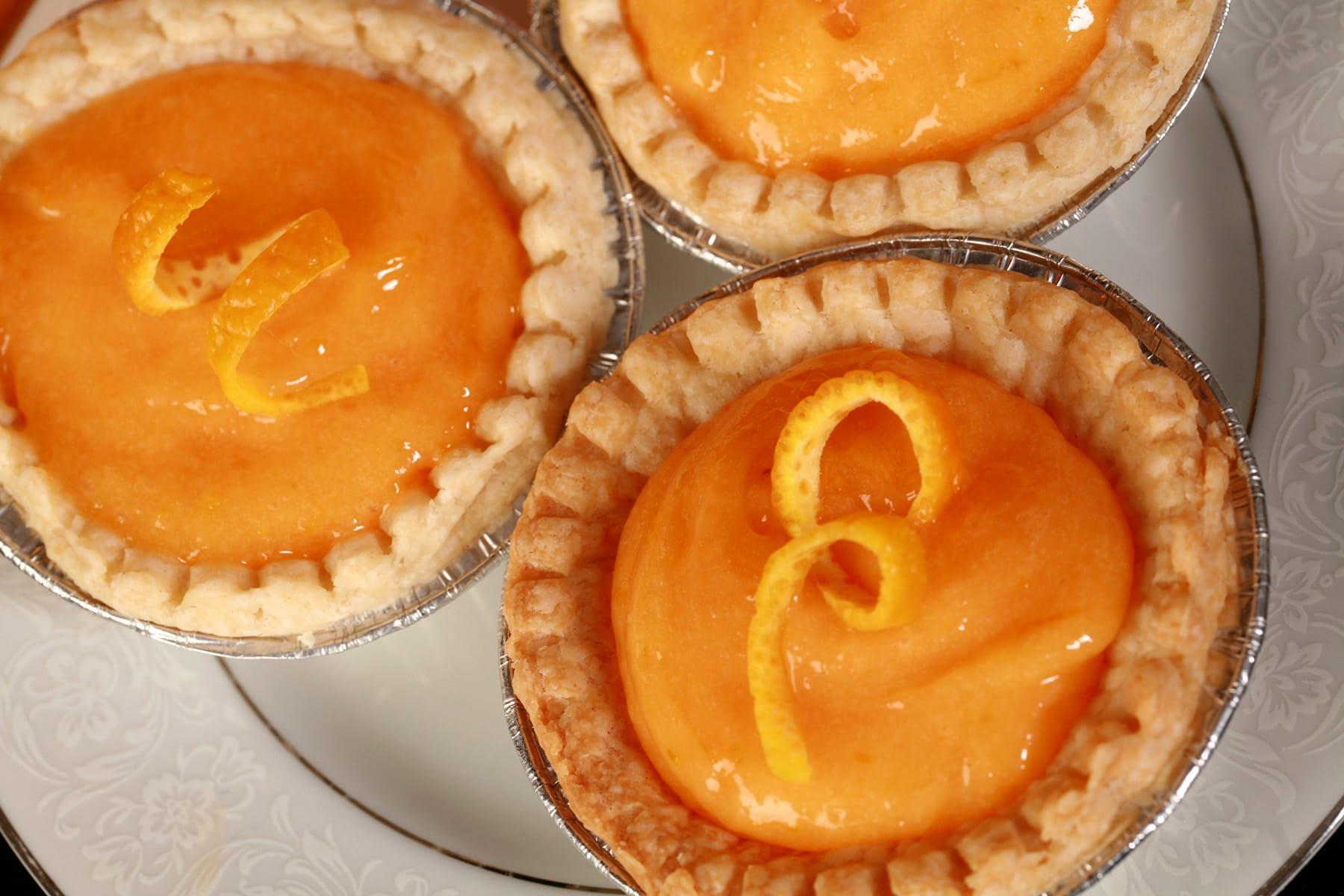 3 orange tarts on a plate.