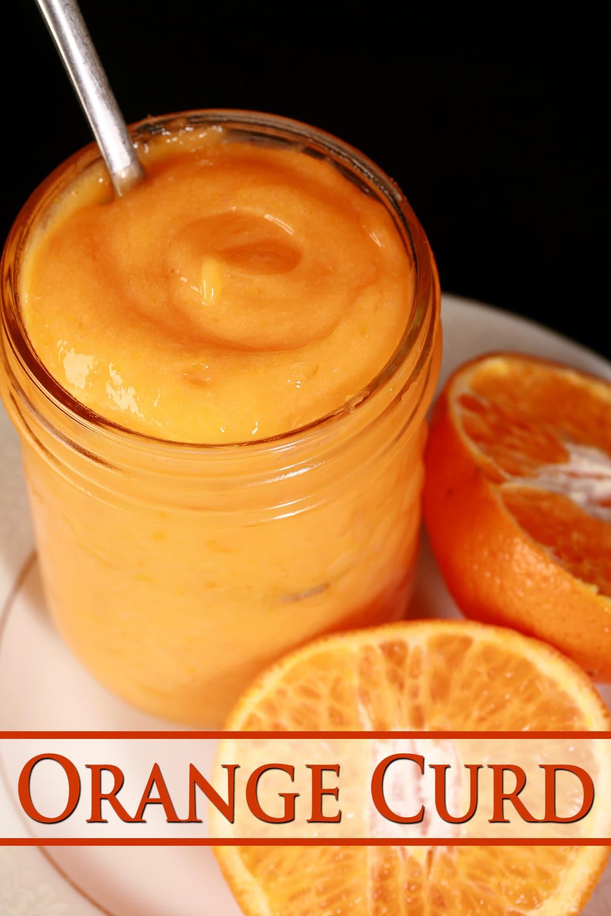A jar of orange curd on a plate, along with a sliced orange.