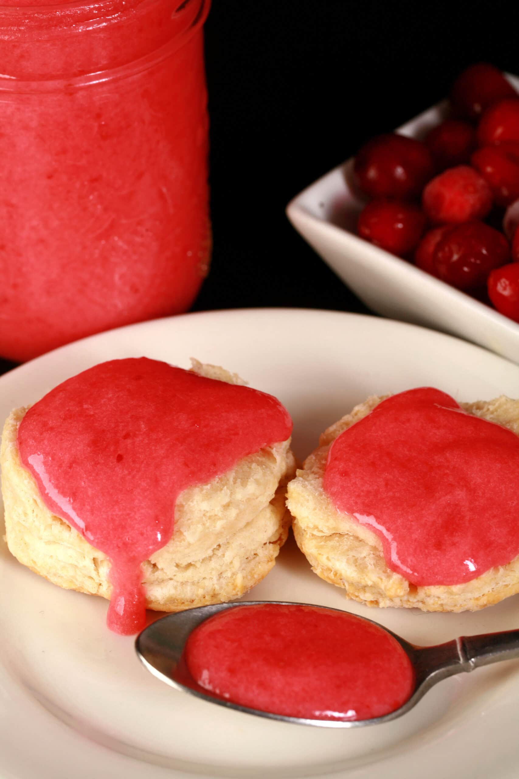 Two biscuits topped with cranberry curd on a plate, with a spoon and jar of curd nearby.