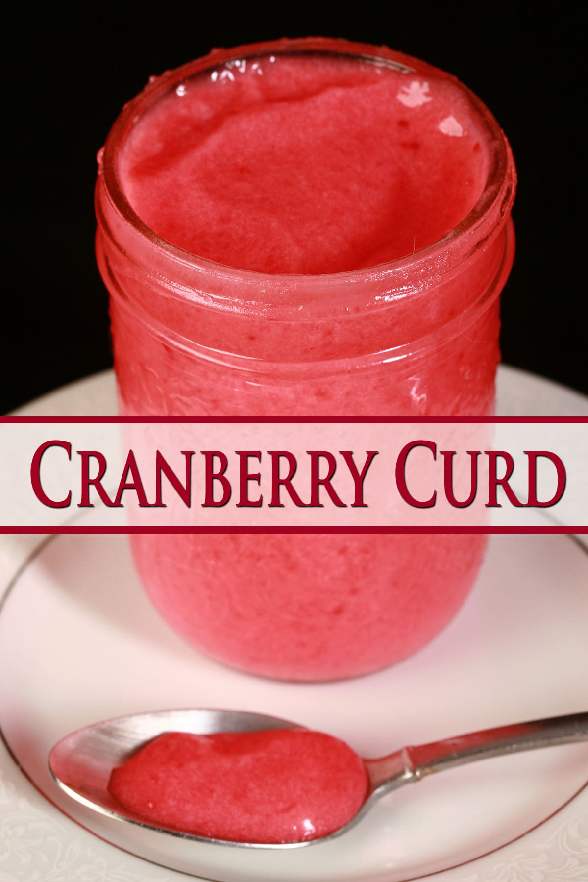 A jar of cranberry curd on a small white plate, next to a spoon with curd on it.