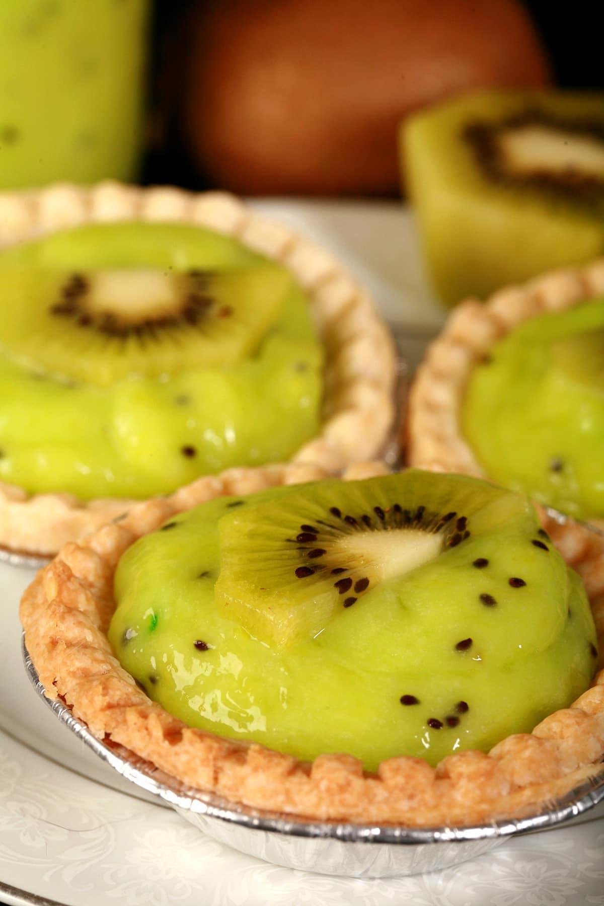 3 Kiwi tarts on a plate.