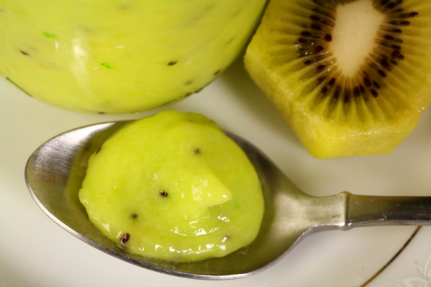 A jar of kiwifruit curd on a plate. There is a spoon of curd next to the jar.