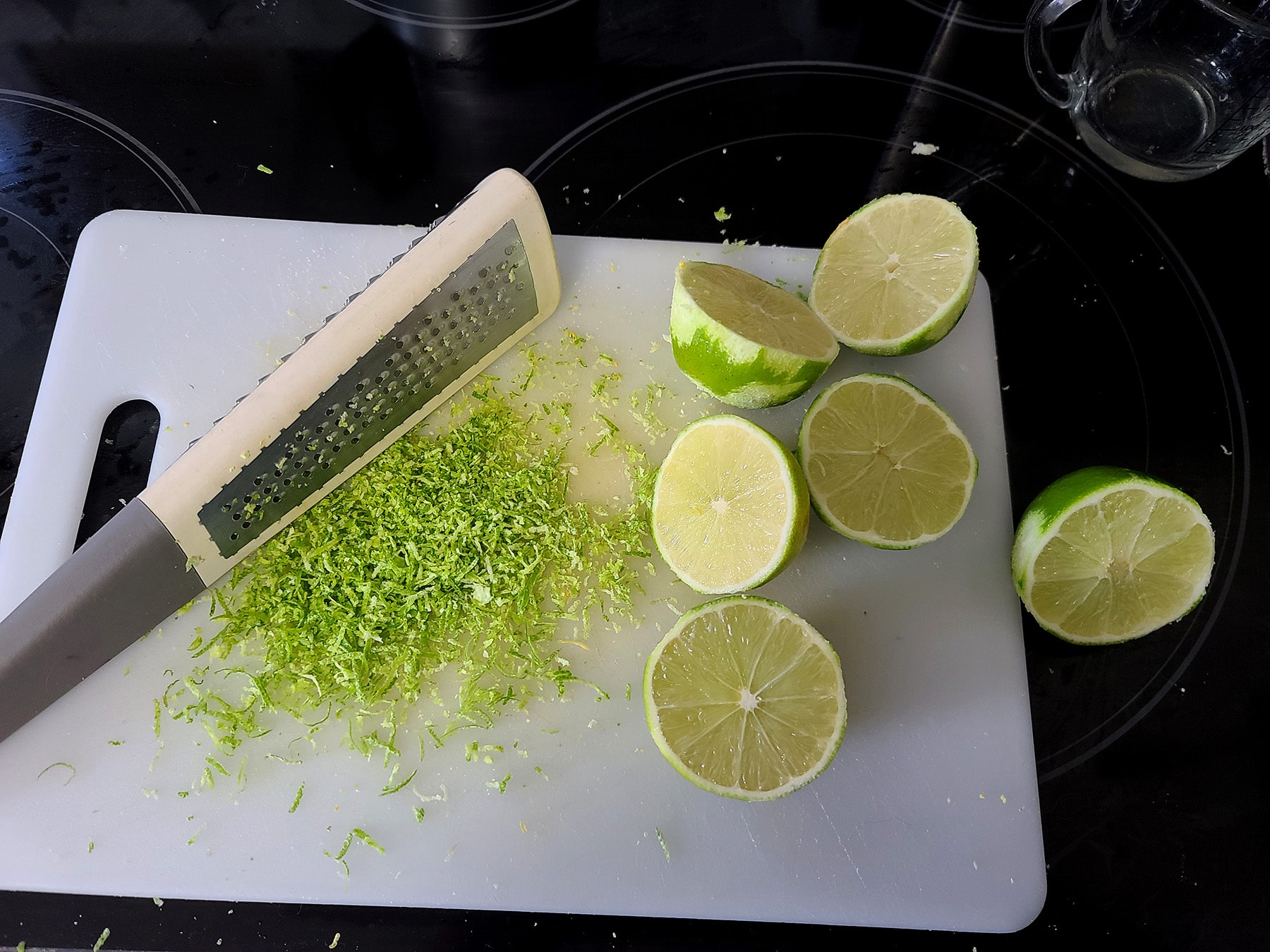 Several limes being zested on a white cutting board.
