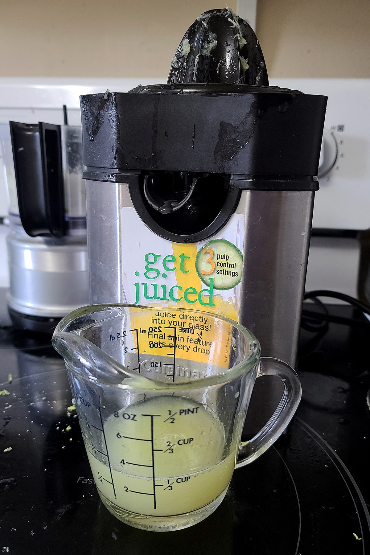 Lime juice pouring out of a juicer.