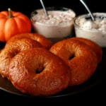 A plate of maple pumpkin spiced bagels. There is a mini pumpkin and 2 dishes of flavoured cream cheese behind the plate.