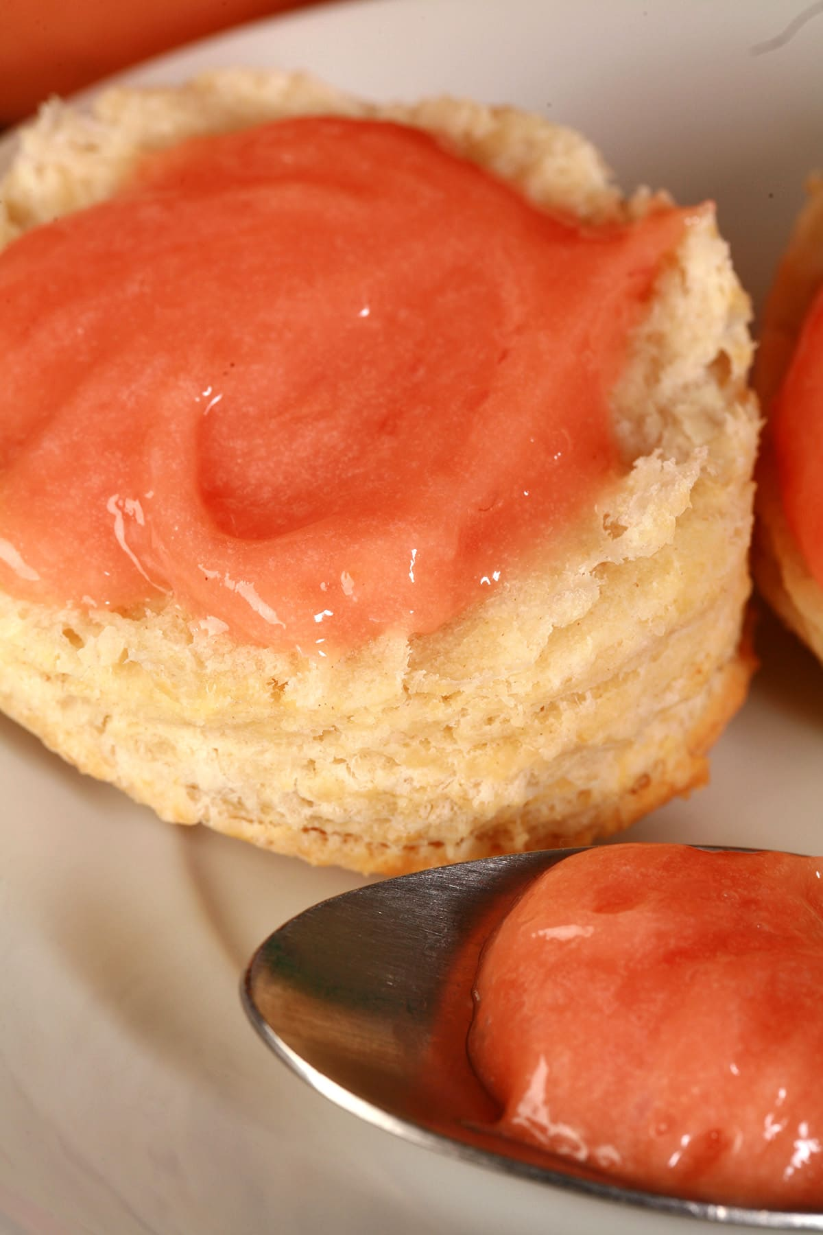 A raspberry curd covered biscuit on a plate, along with a spoon of the pink curd.