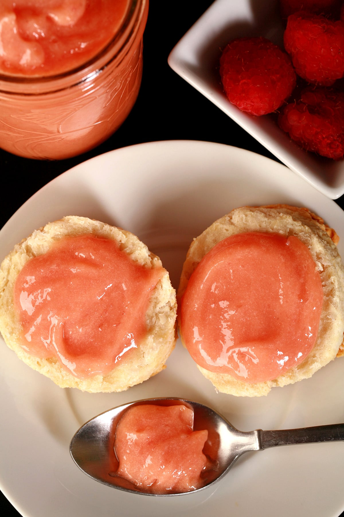 Two raspberry curd covered biscuits on a plate, along with a spoon of the pink curd.