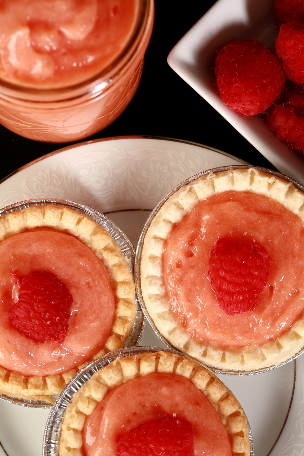 3 raspberry tarts on a plate, each topped with a fresh raspberry.