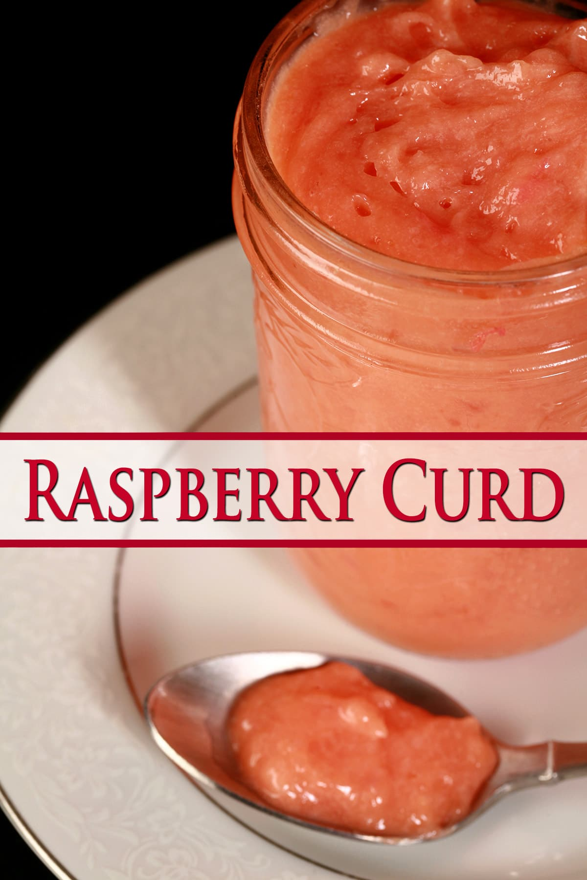 A jam jar of raspberry curd on a plate, next to a spoon with the pink curd on it.