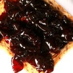 A slice of toast spread with small batch cherry jam.