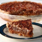 A slice of Southern Comfort pecan pie, in front of the whole pie.