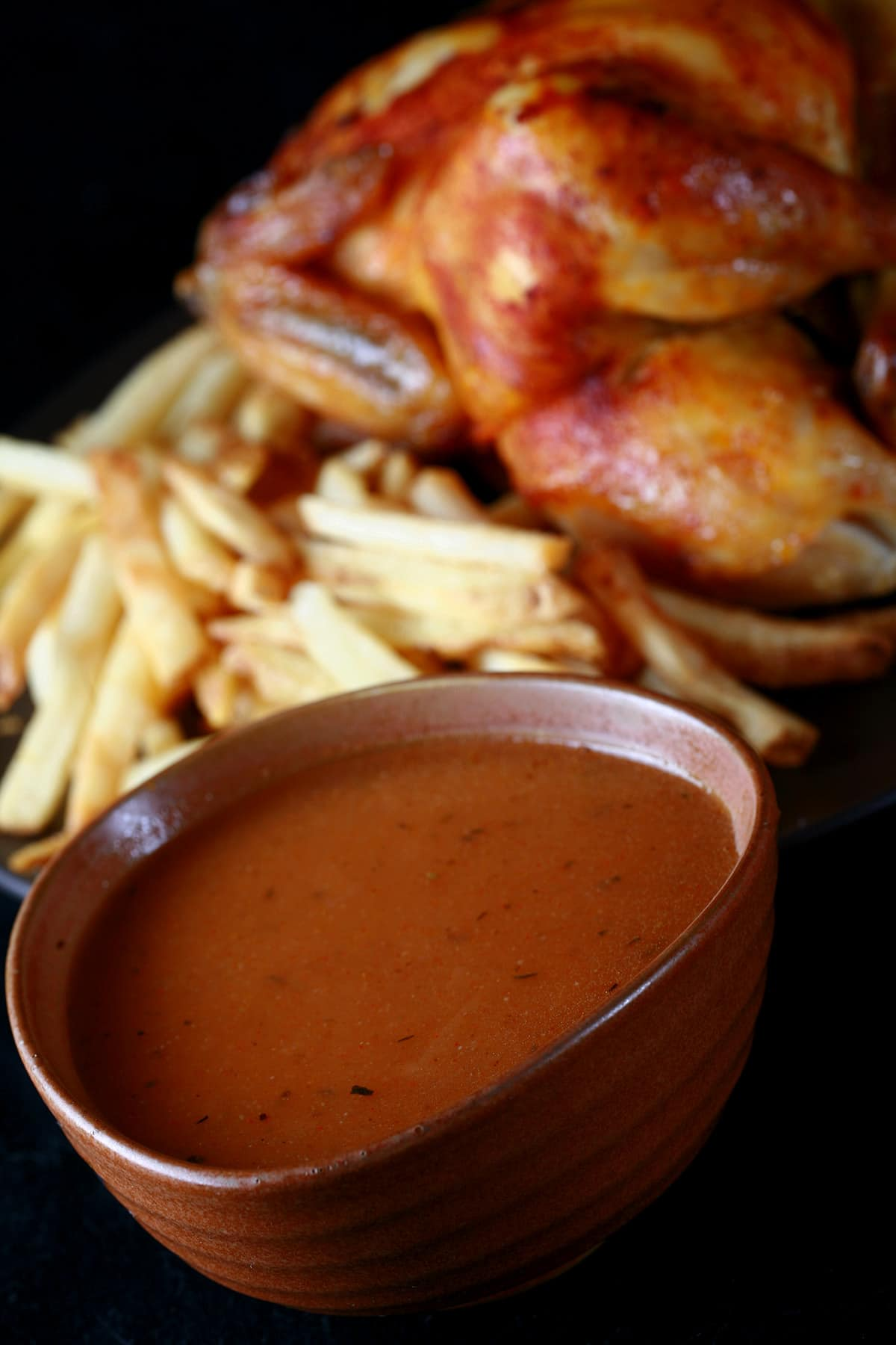 A large bowl of replica Swiss Chalet Sauce next to a roasted chicken and fries.