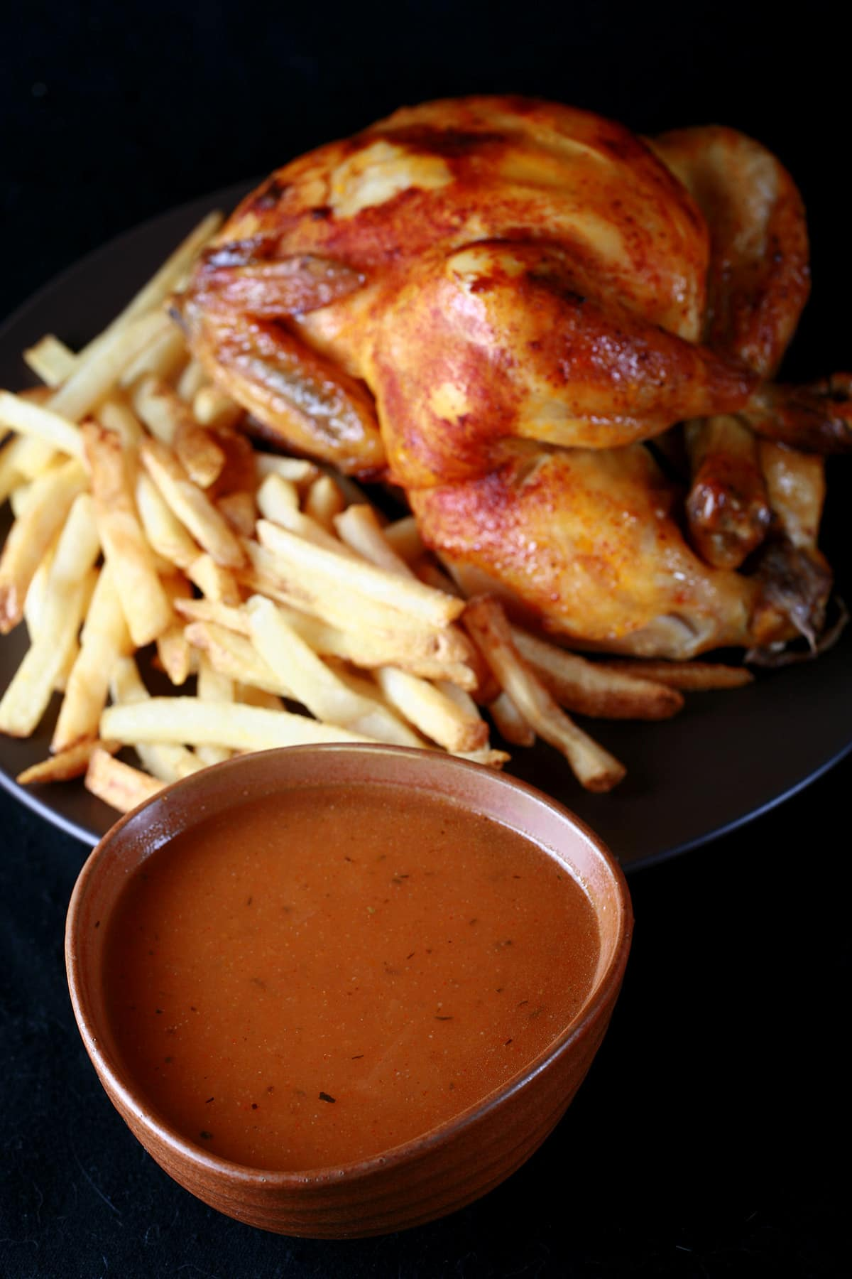 A large bowl of copycat Swiss Chalet Sauce next to a roasted chicken and fries.
