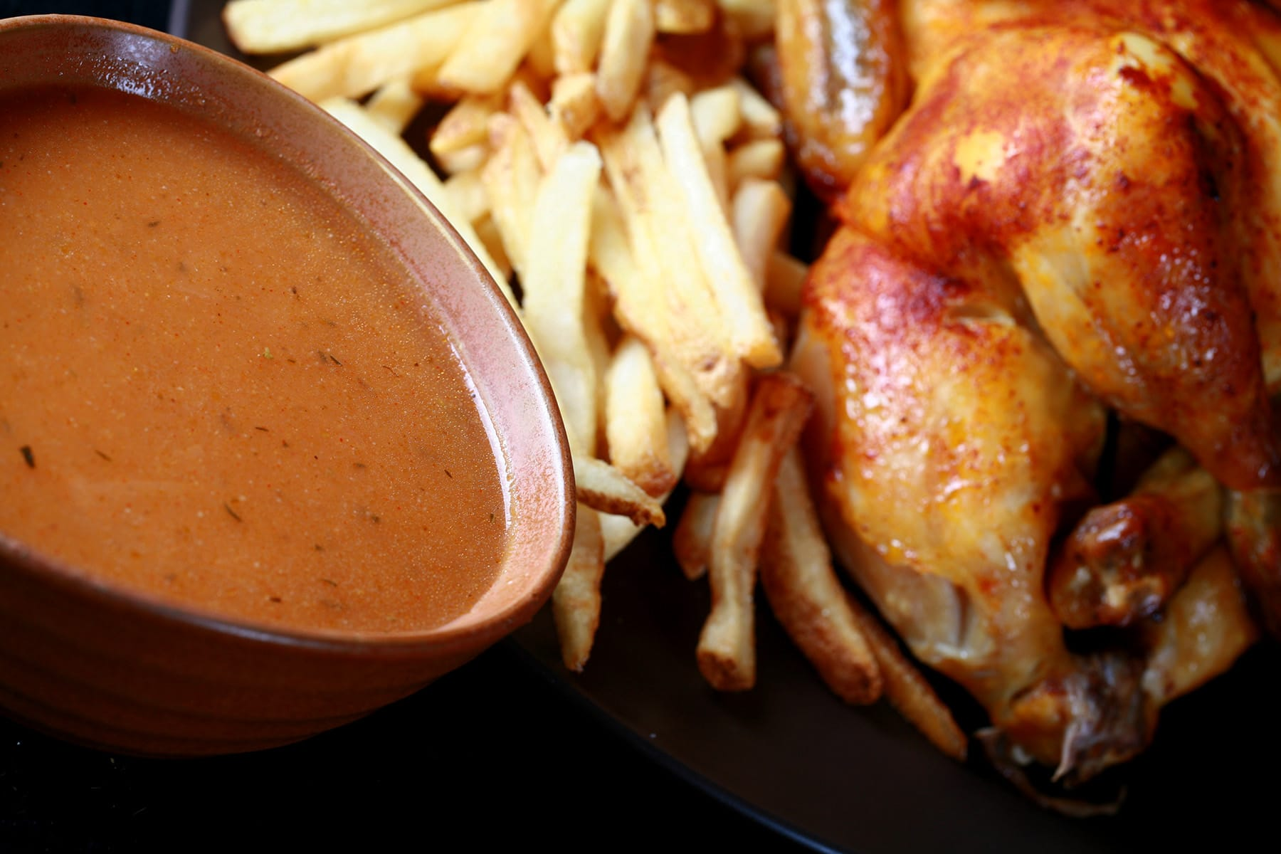 A large bowl of homemade Swiss Chalet Sauce next to a roasted chicken and fries.